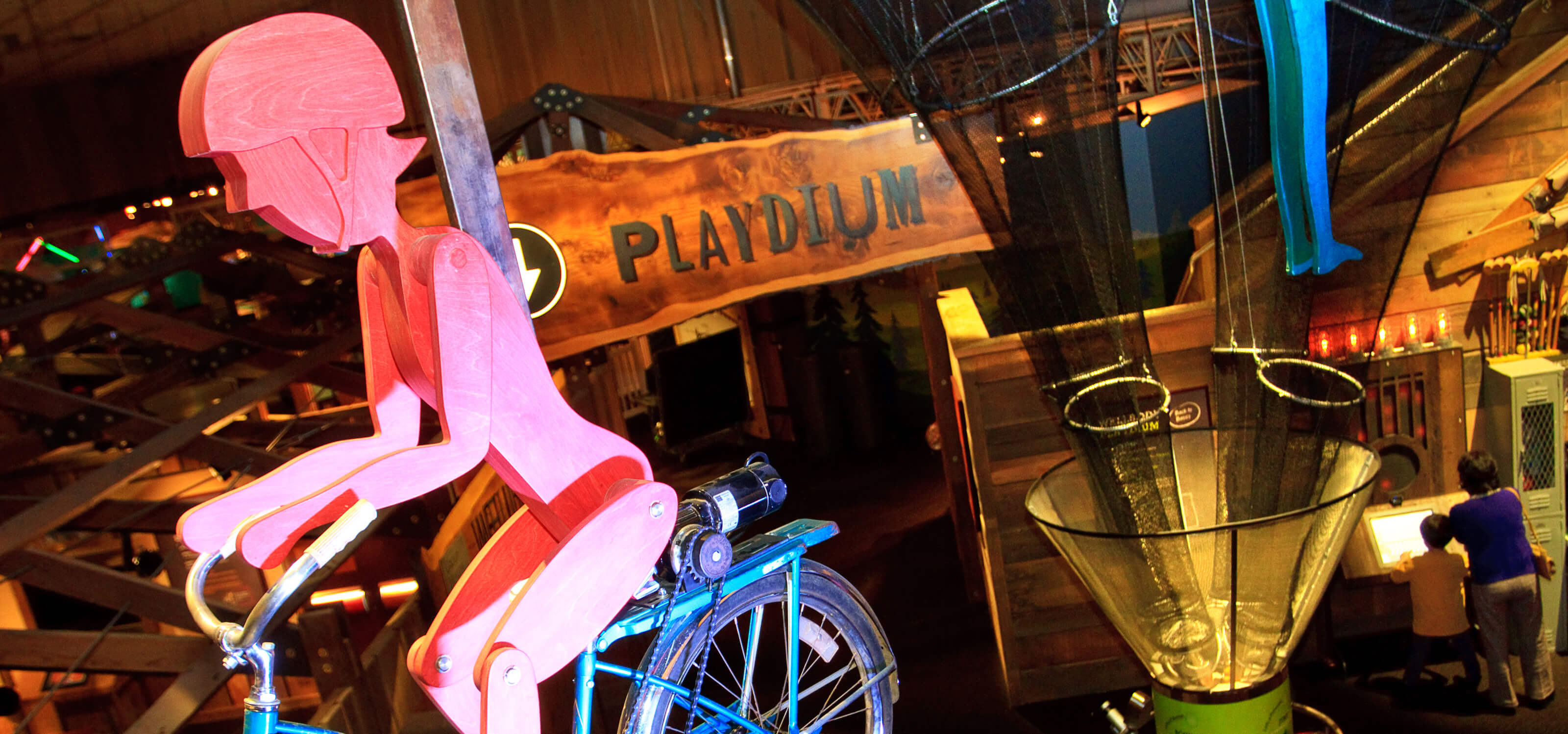 View from above the Playdium section, with a red wooden figure riding a bike in the foreground