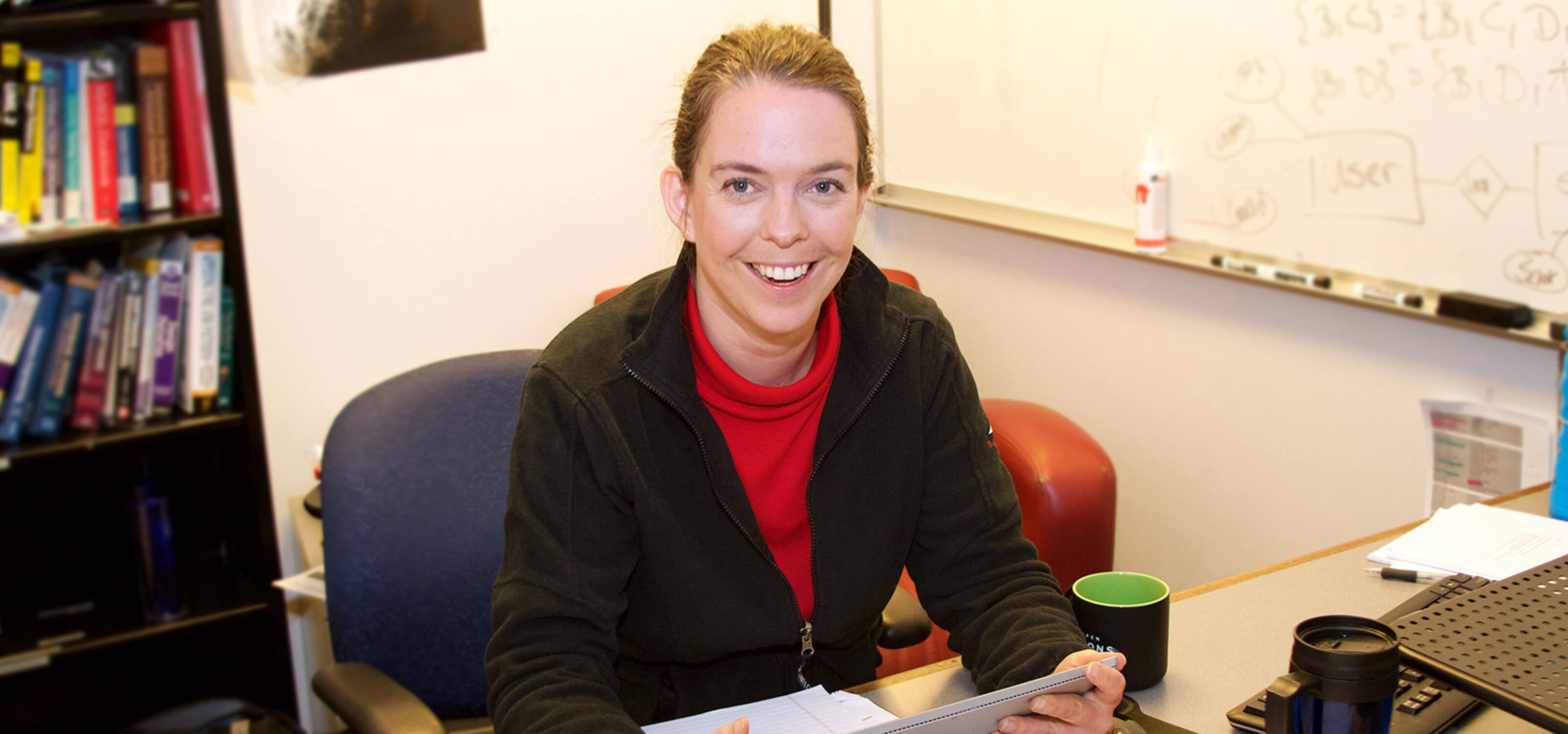 Professor Eva Iwer smiling while sitting at her desk in her DigiPen office