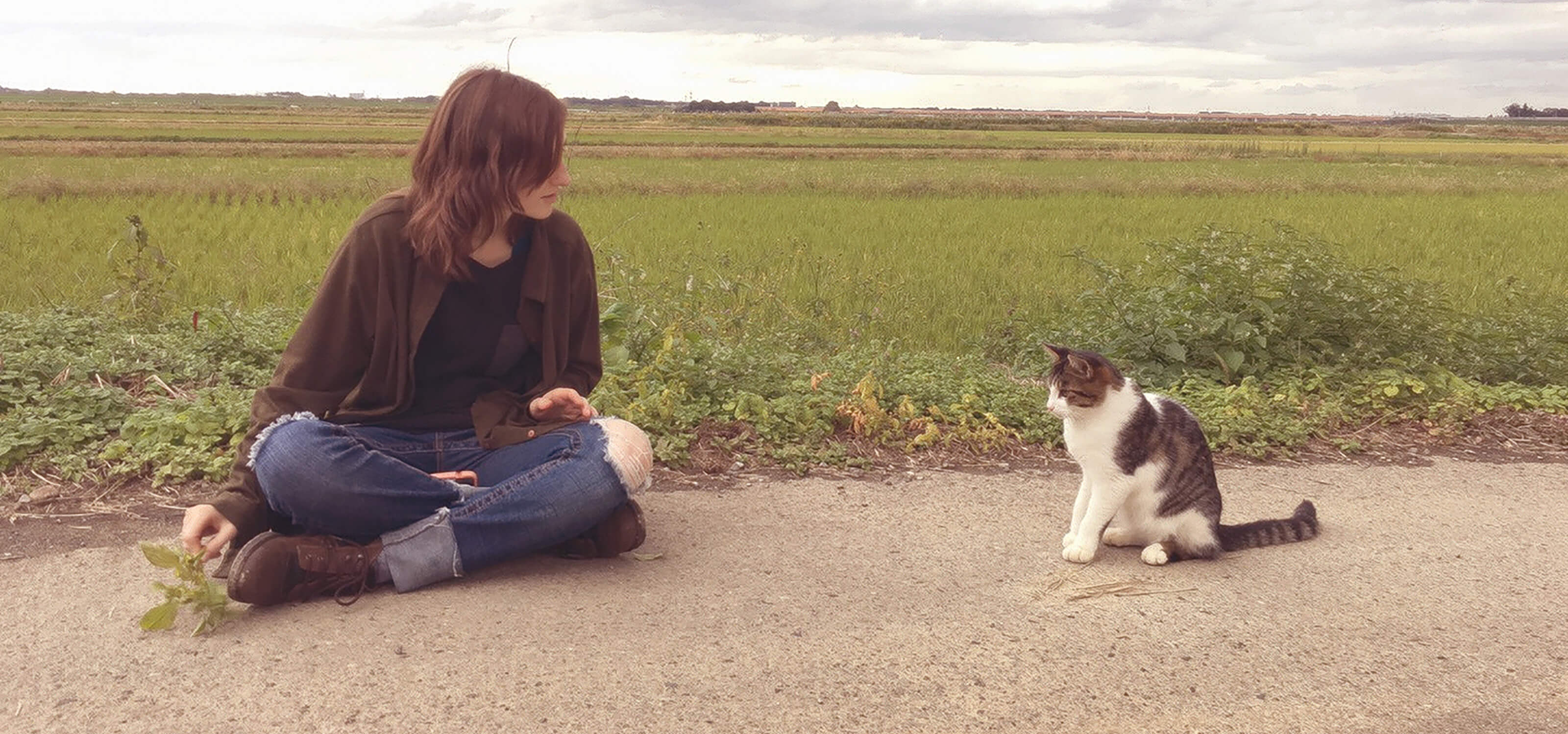 DigiPen alumna Heather Gross sitting on a dirt road in Japan, trying to coax a cat to come over to her