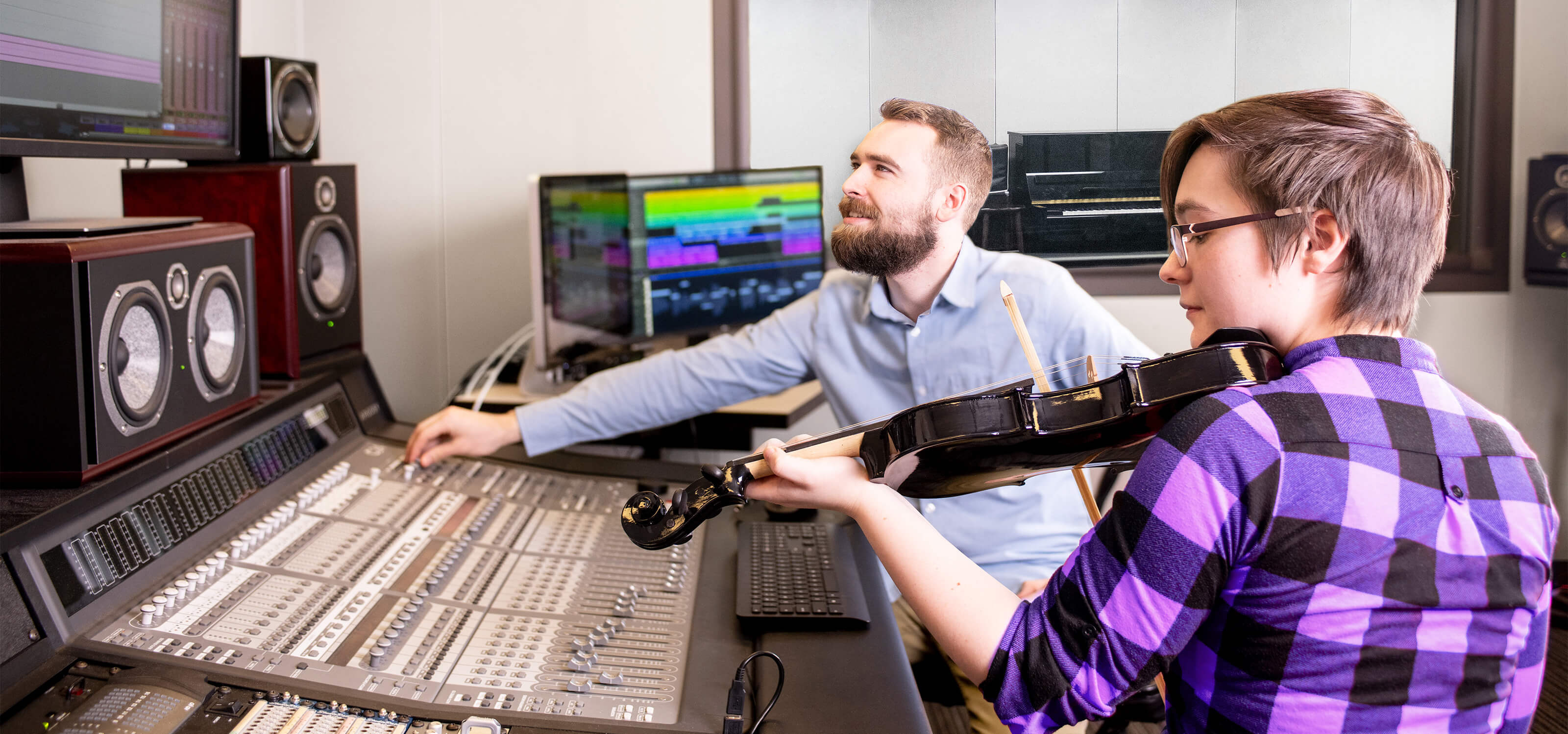 A DigiPen student plays violin next to a large audio mixing board.
