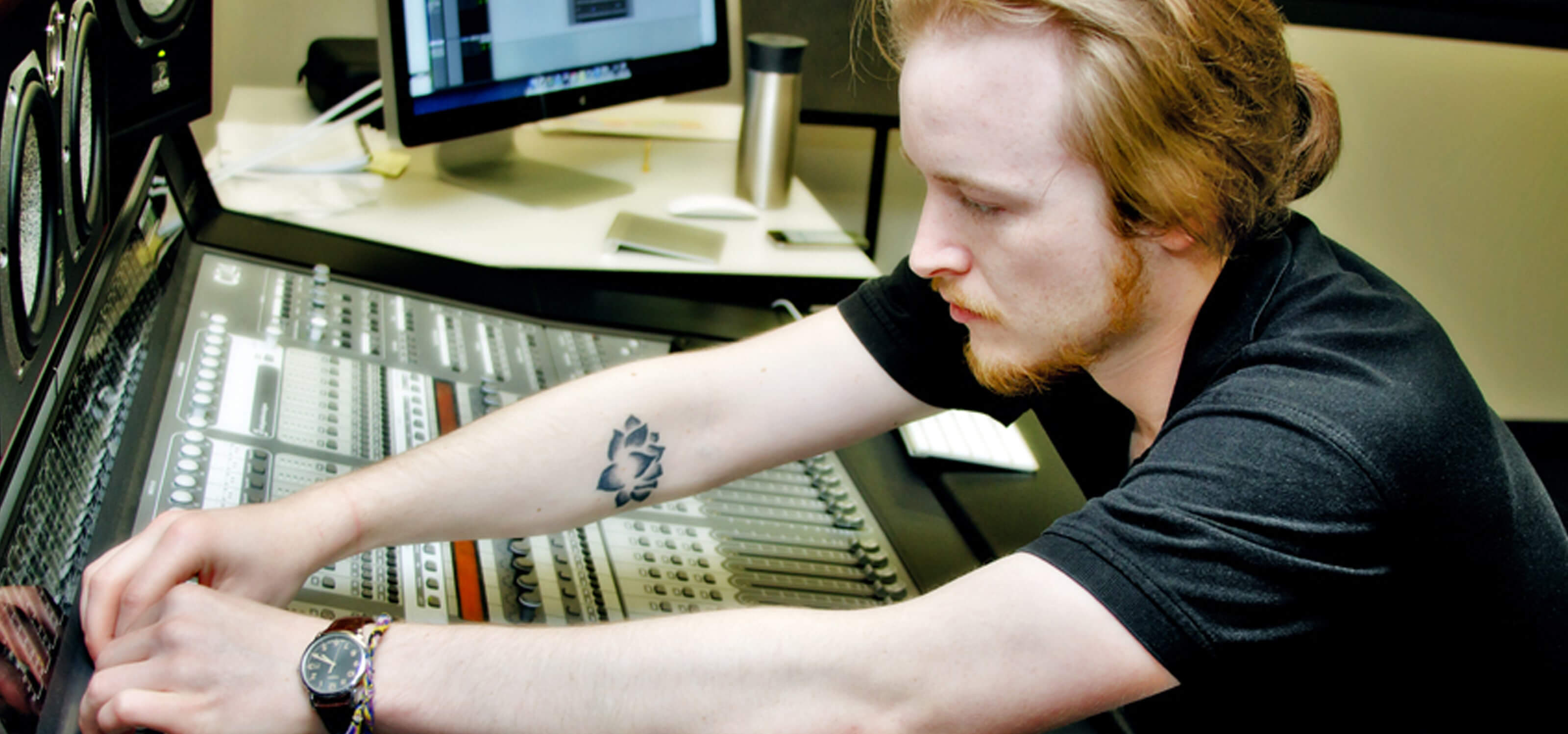 DigiPen student Ian Shores adjusting knobs on a sound board in a DigiPen recording studio