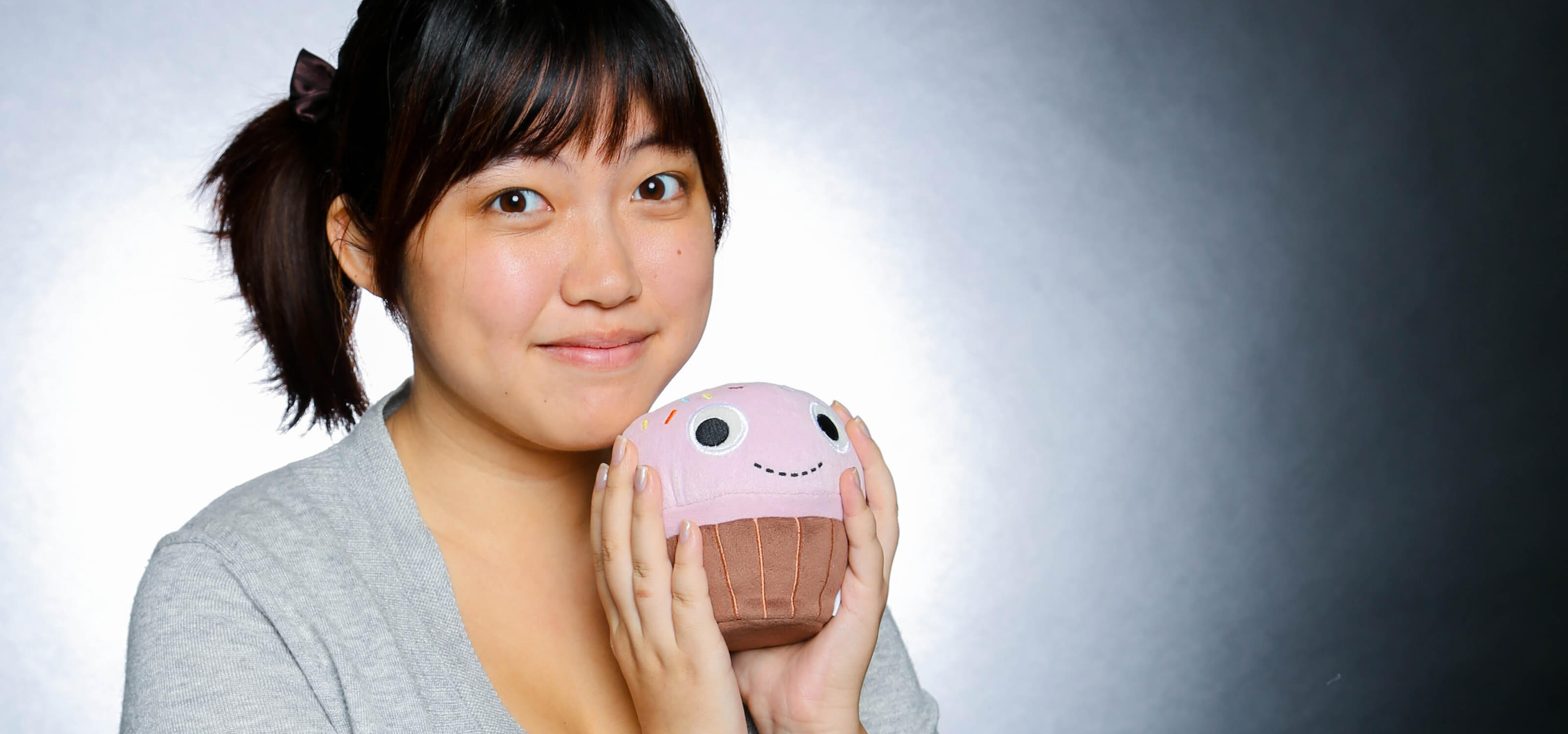 DigiPen alumna Jessica Nam posing with a cupcake-shaped plush toy