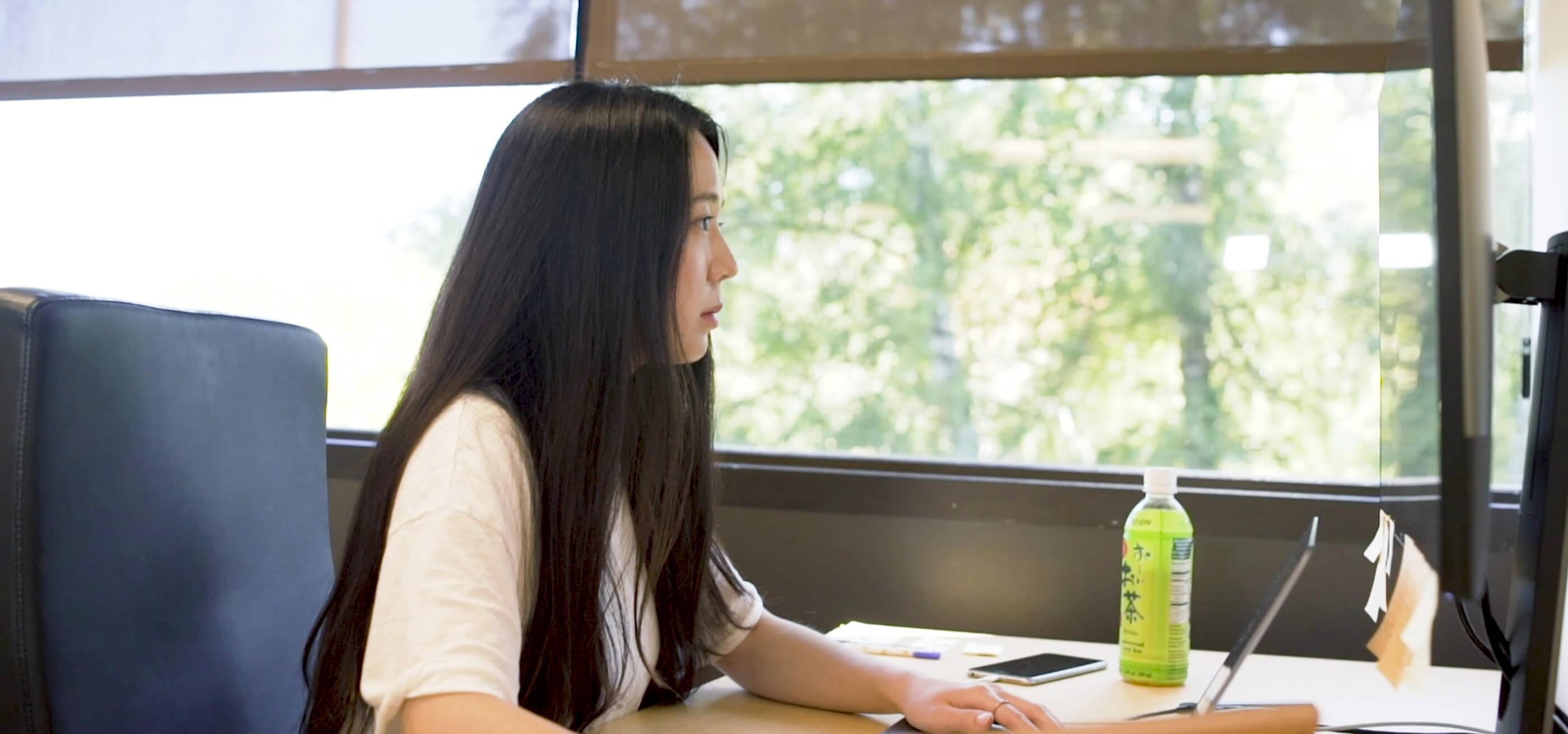 DigiPen grad Jiyun Kang sits at computer workstation
