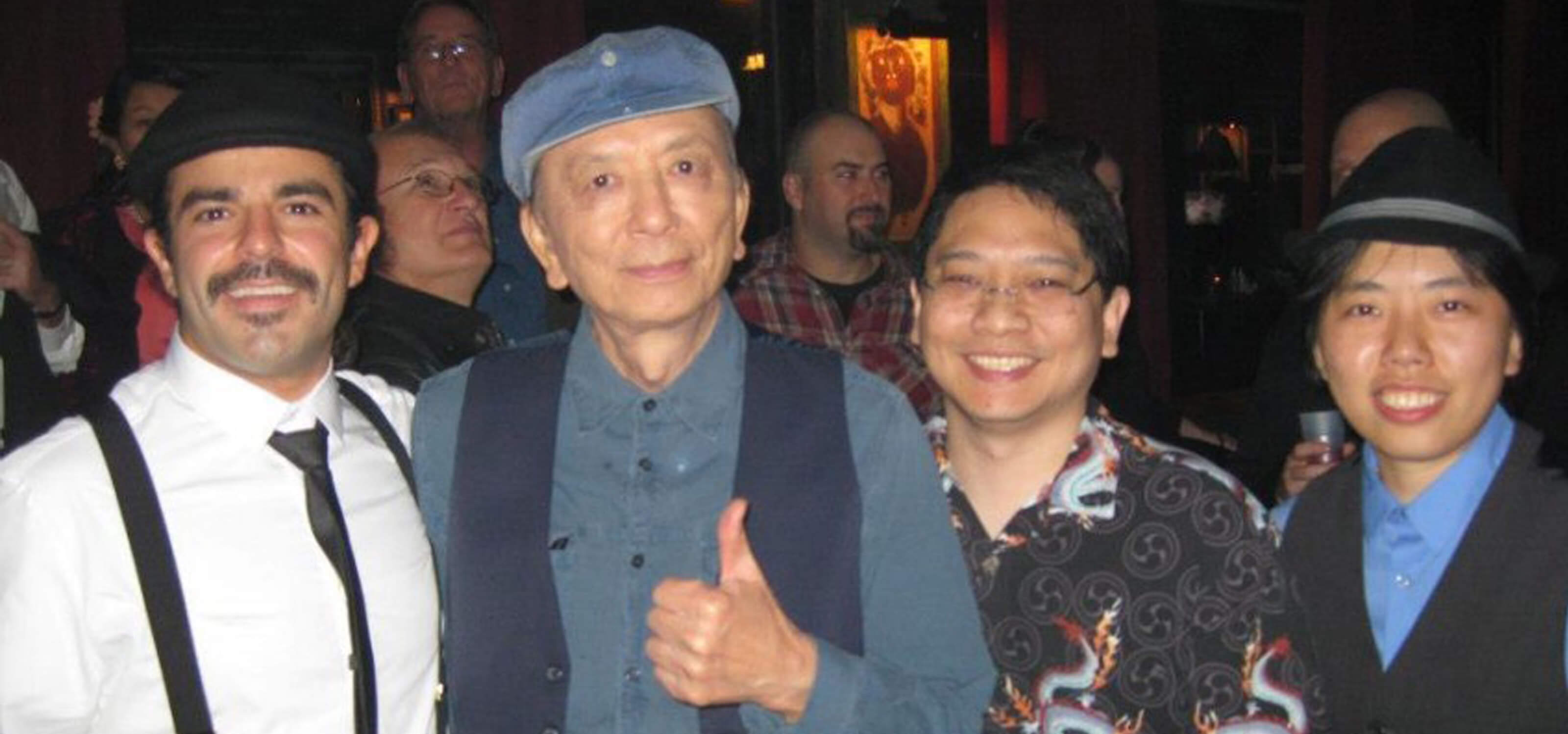 Photo of DigiPen alumna Joanna Leung and two of her colleagues with Call of Duty voice actor James Hong at a launch party