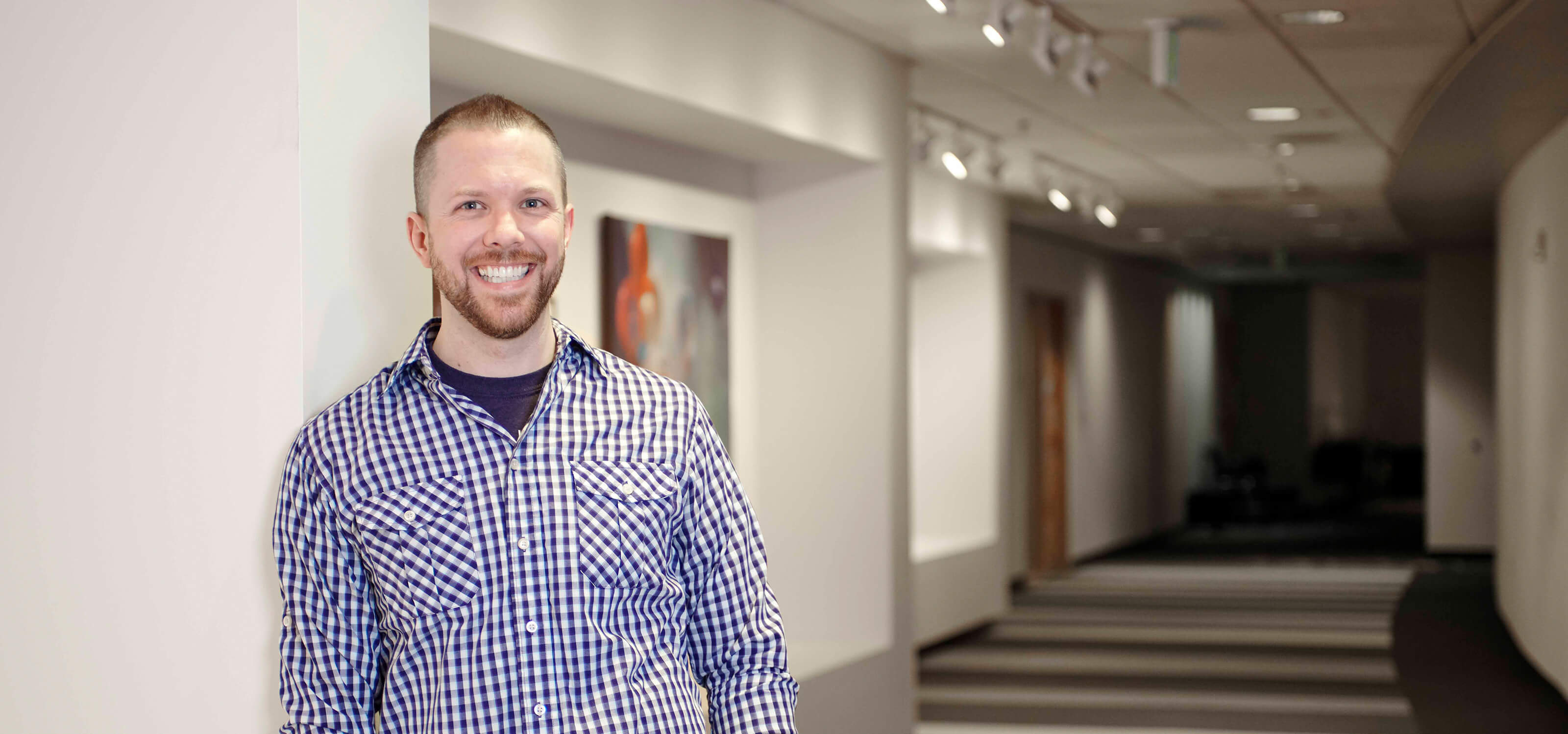 Game Software Design and Production Senior Lecturer Justin Chambers smiles in a DigiPen hallway.