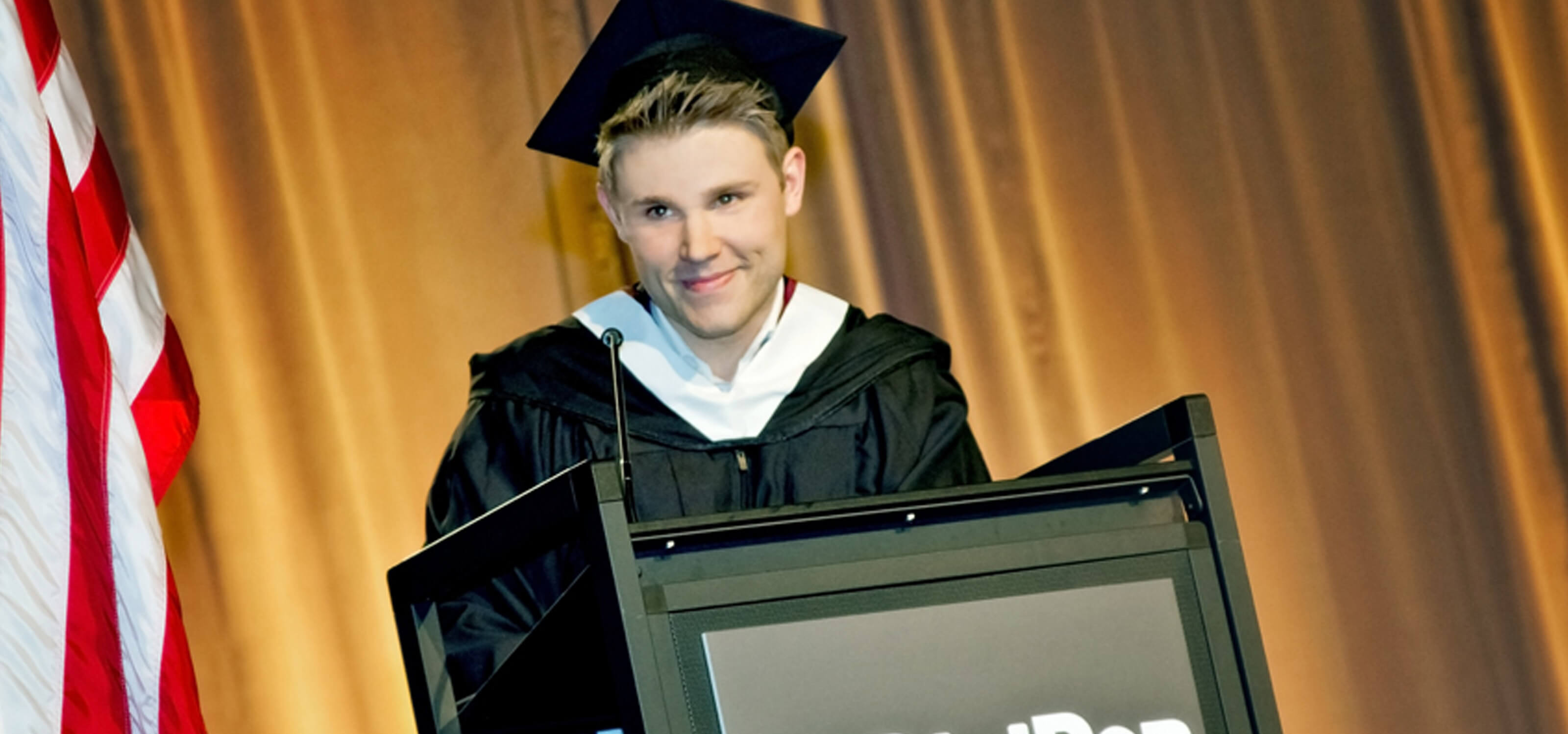 DigiPen graduate Kevin French speaking at the podium at the 2013 commencement ceremony