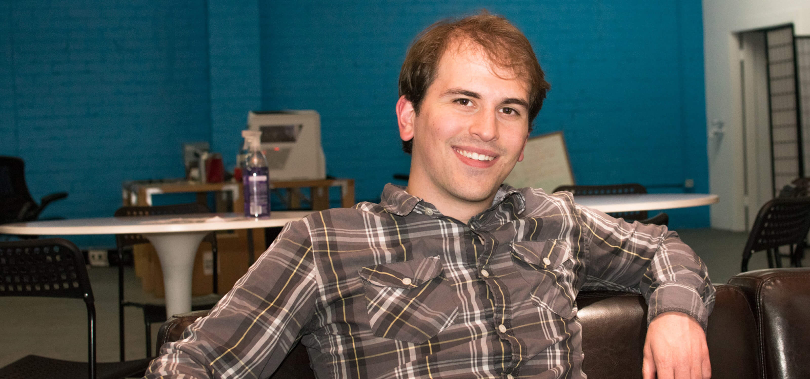 DigiPen alumnus Logan Fieth smiling while sitting on a couch