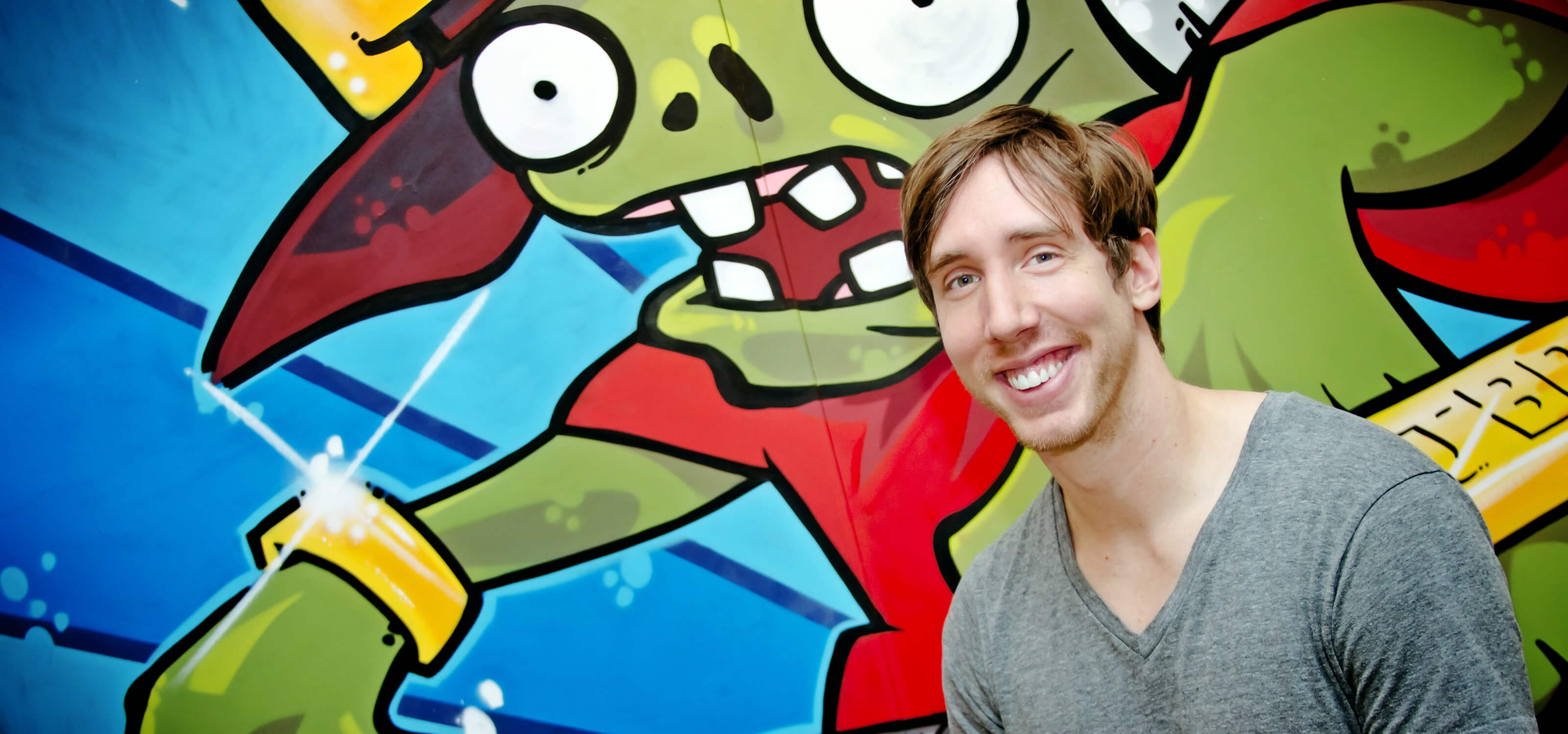 DigiPen BFA alumnus Mark Barrett smiling in front of large grafffiti-style wall painting of a zombie at PopCap's office