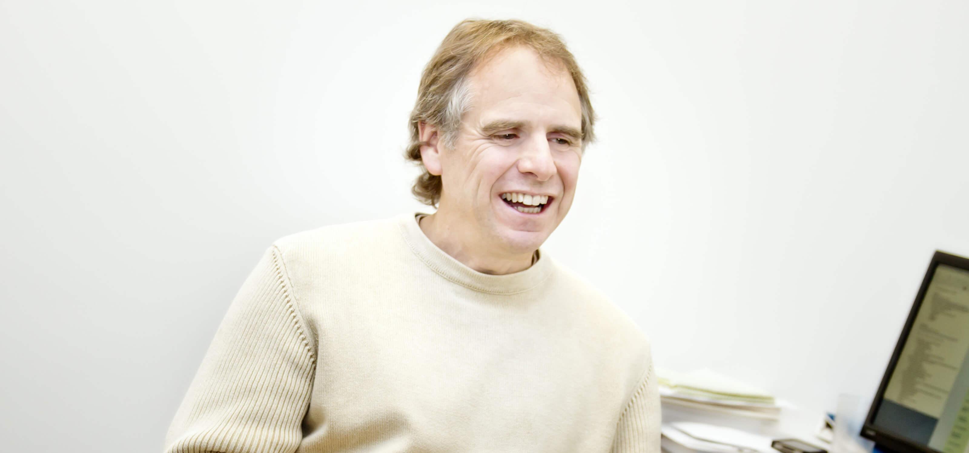 DigiPen digital arts lecturer Mark Henne smiling in his DigiPen office