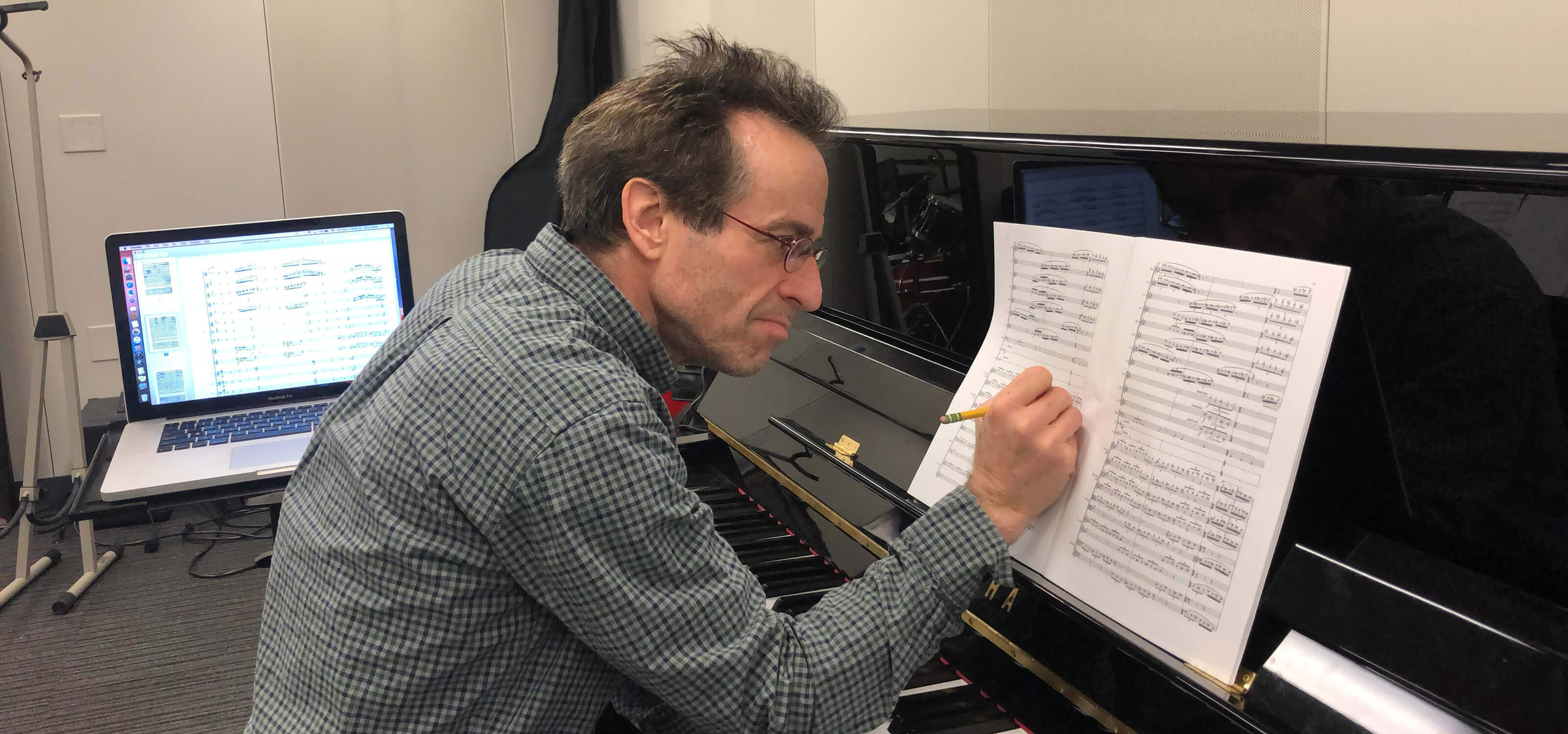 DigiPen music department chair Bruce Stark sitting at a piano, making notations on sheet music