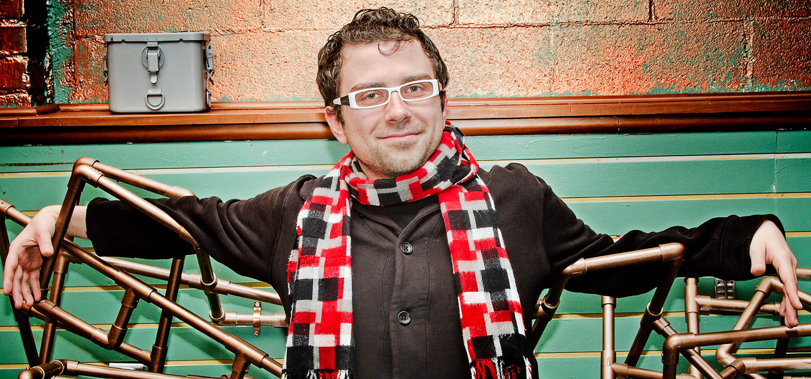 DigiPen alumnus Nate Martin in a plaid scarf, black coat and white-framed glasses with a prop made of bronze-colored pipes