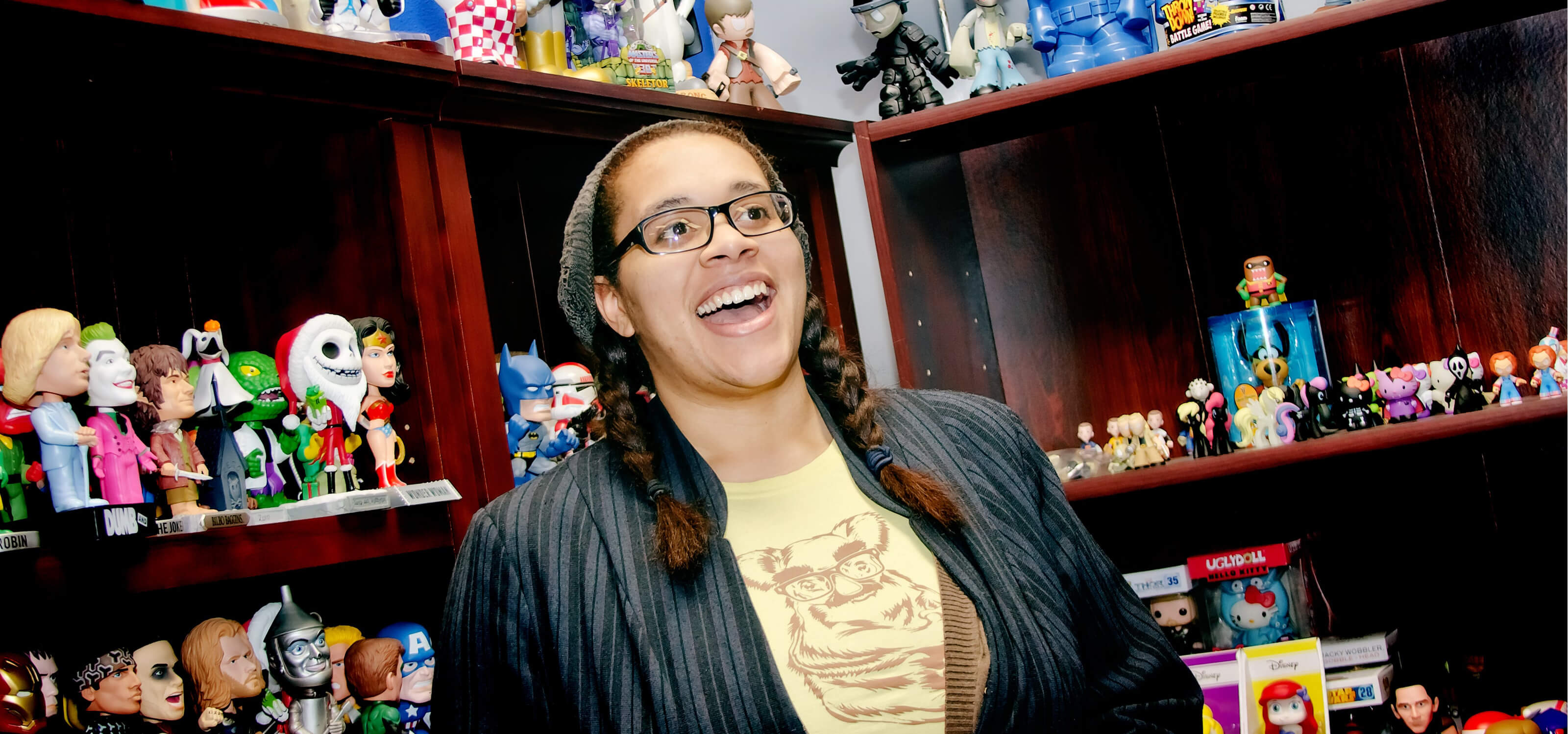 DigiPen BFA alumna Nnenna Ijiomah smiling in front of bookshelves filled with Funko figurines at the Funko office