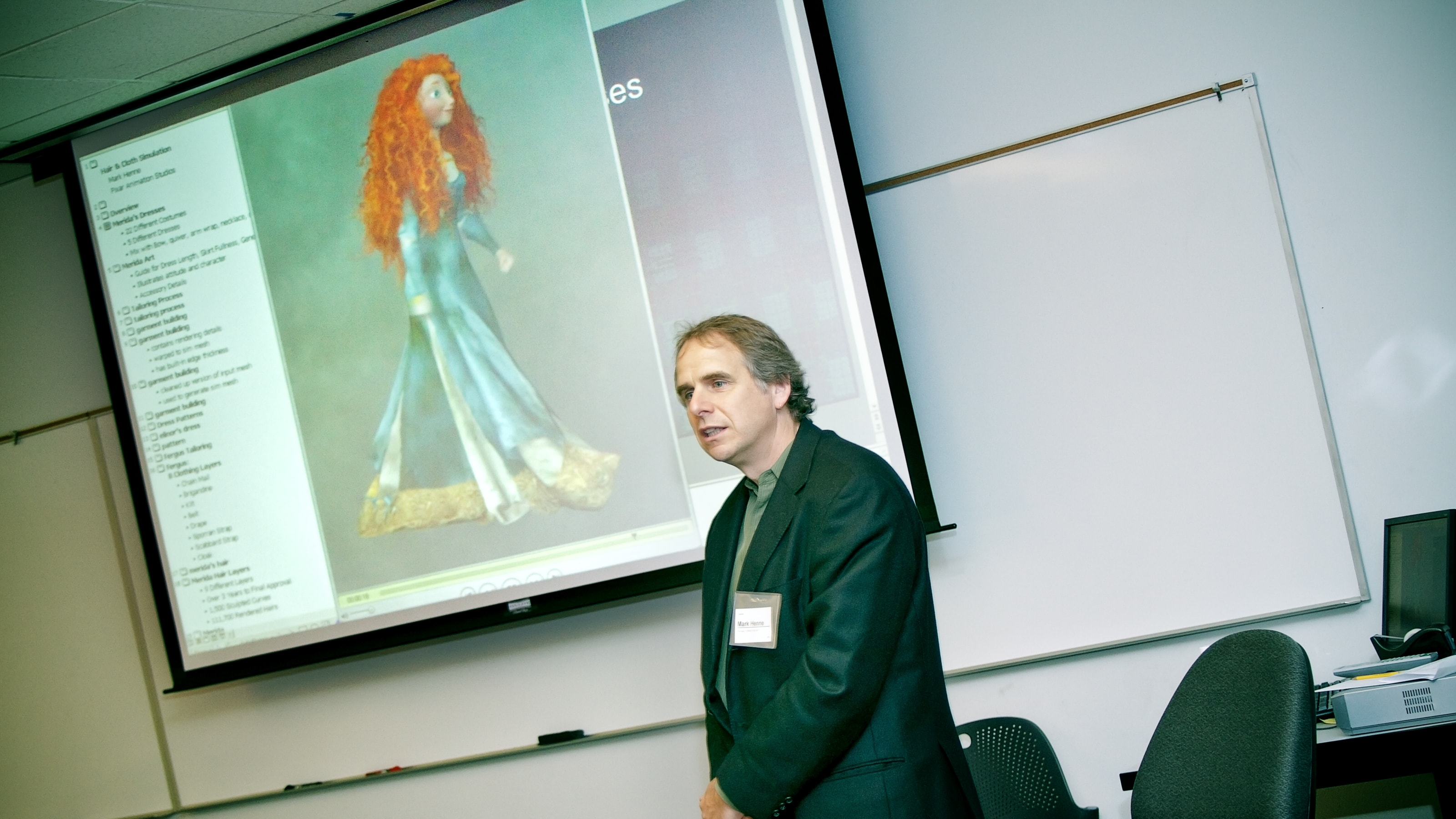Pixar's Mark Henne speaking in front of a screen showing Princess Merida from the animated movie Brave