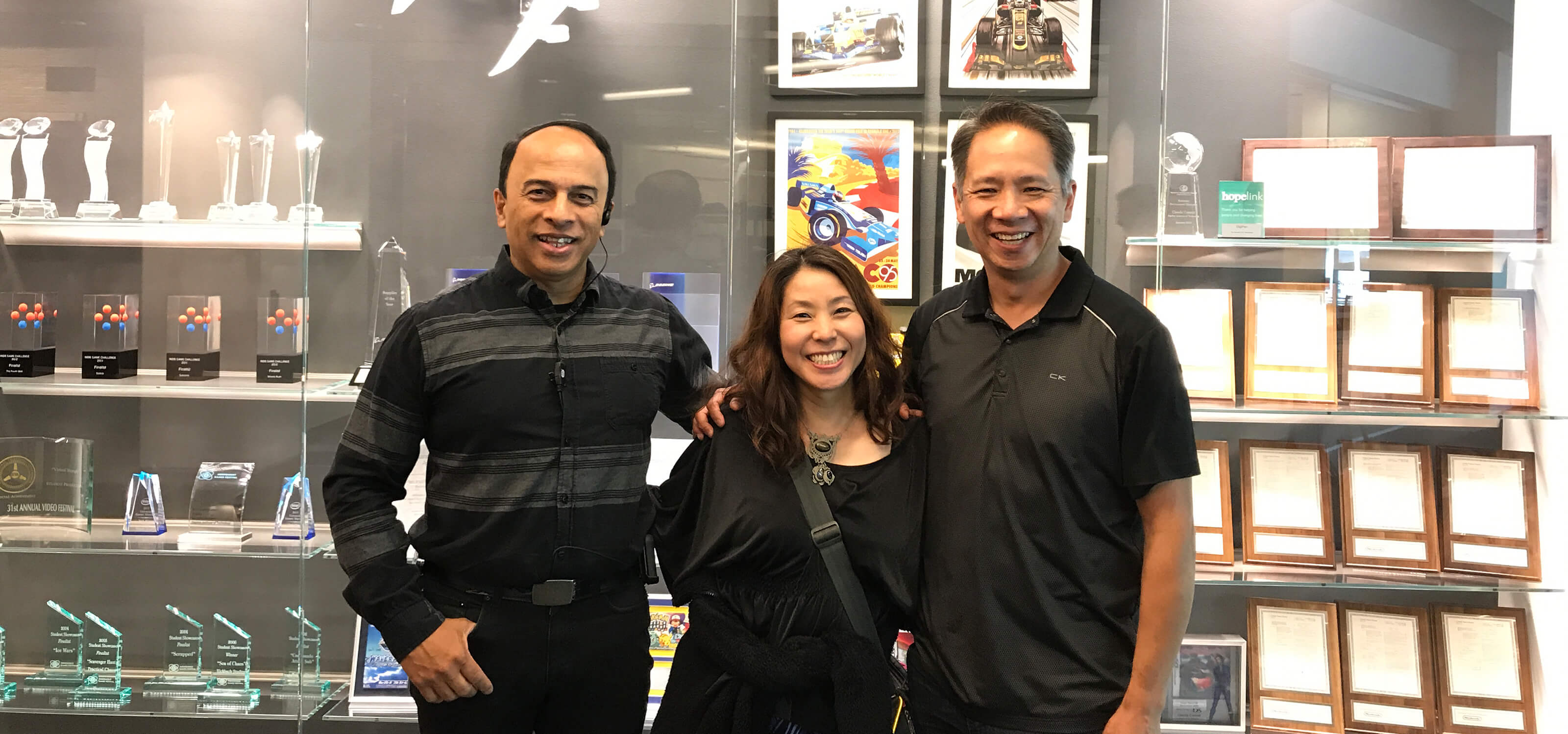 Satomi Asakawa stands next to her former DigiPen professors Ray Yan and Melvin Gonsalvez.
