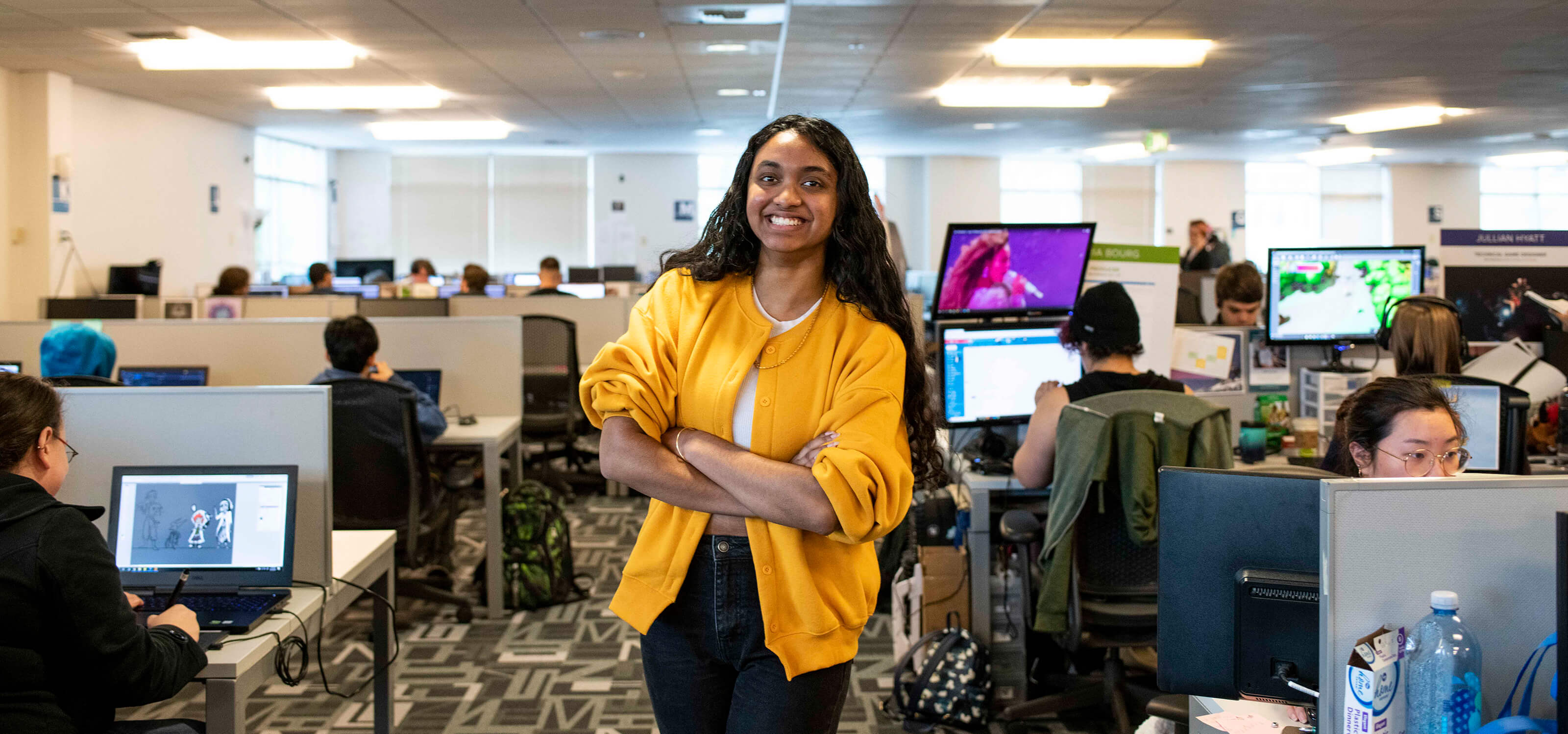 Student Shannon Parayil smiles and stands in the Tesla computer lab on campus, in between rows of team spaces where students are working on projects.