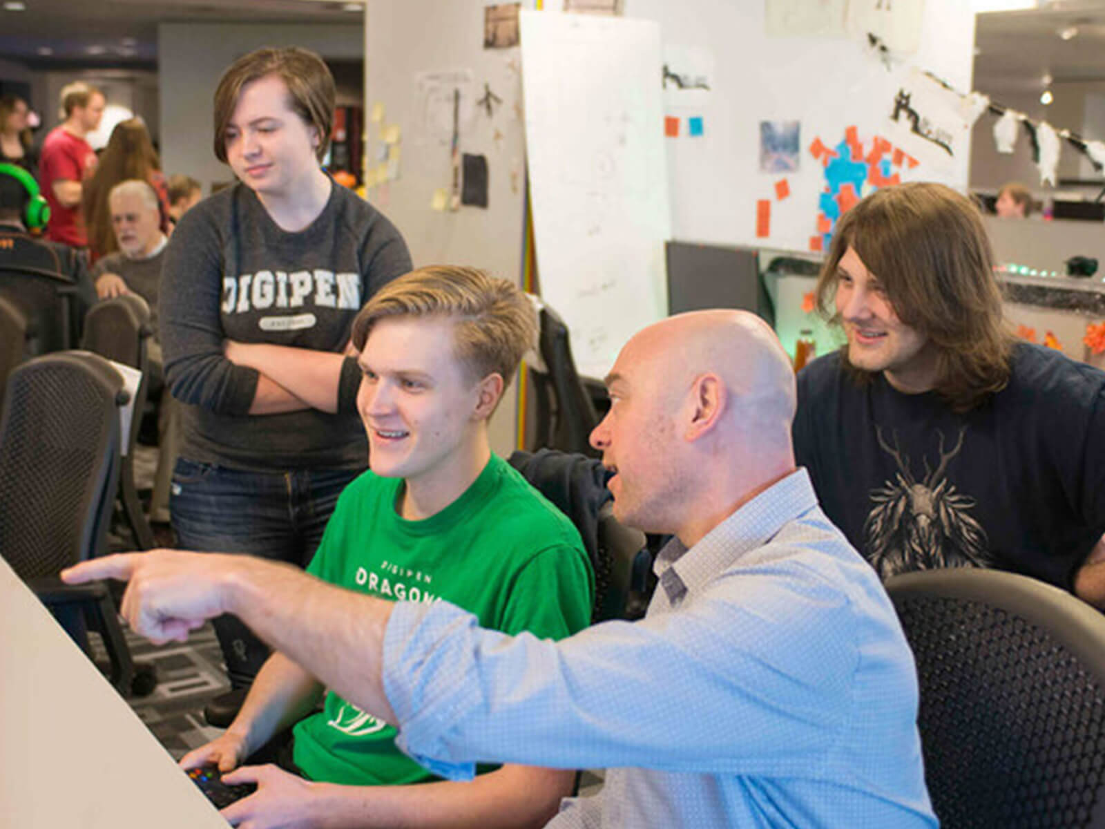 A DigiPen professor points to three students' game team project on a computer in a campus production lab.