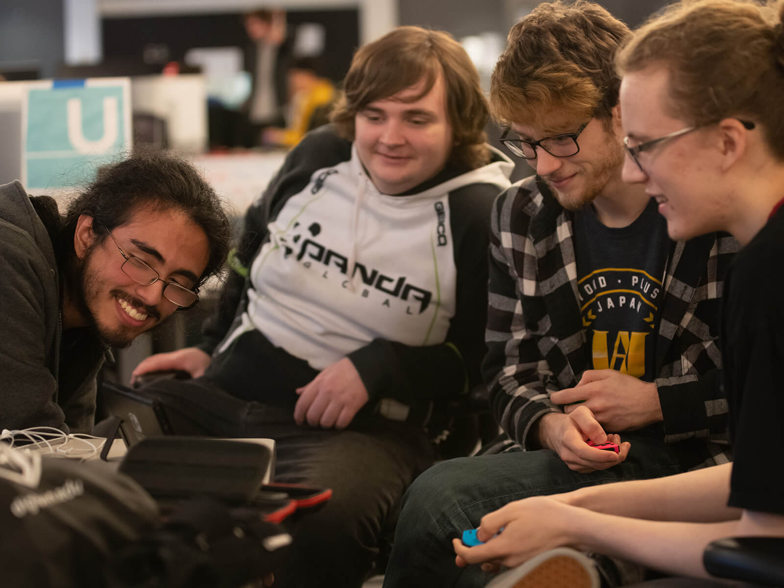 Four DigiPen game teammates smile as they look at their project on screen.