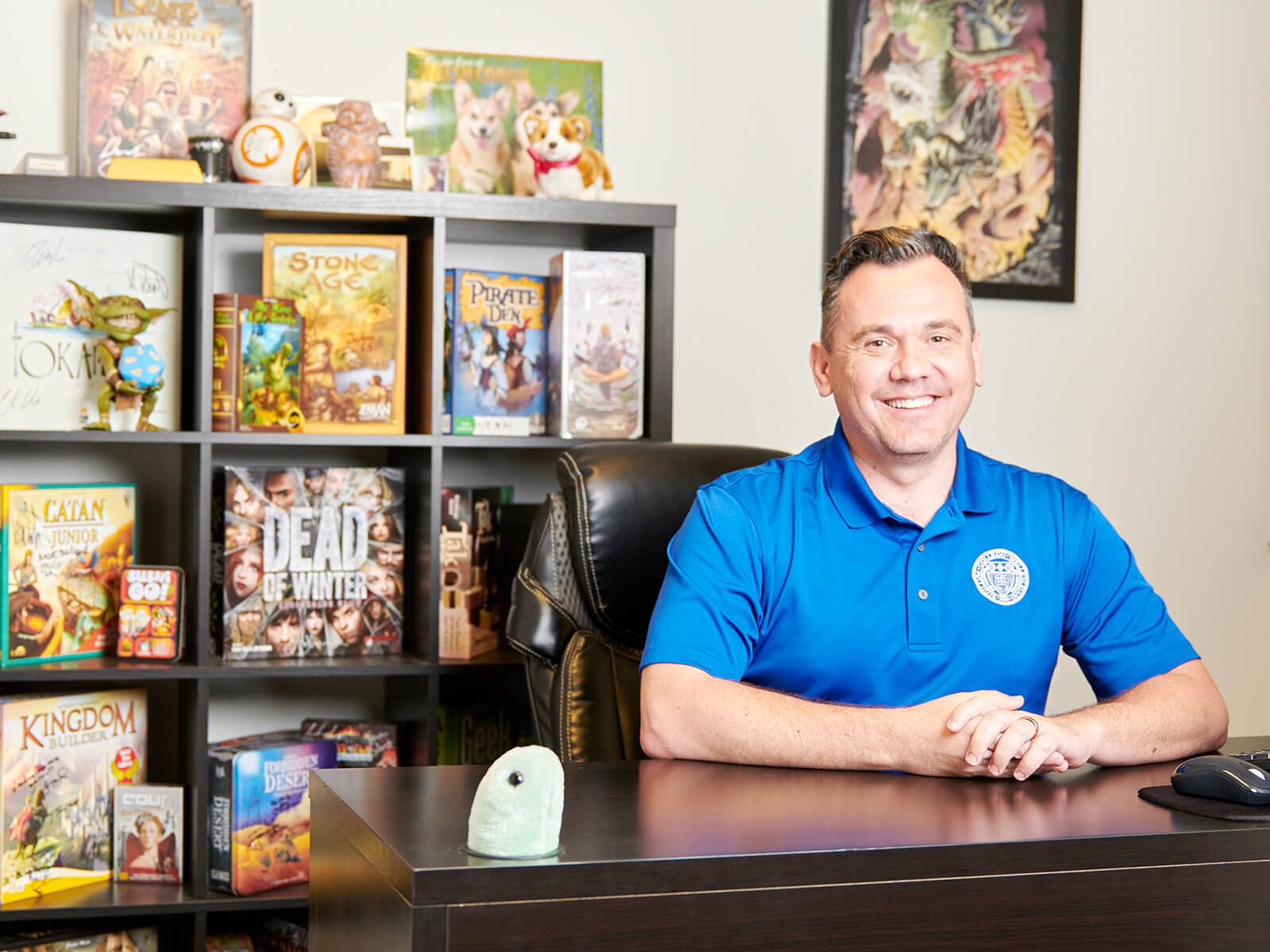 Senior game design lecturer Boyan Radakovich smiles in his office full of tabletop games.