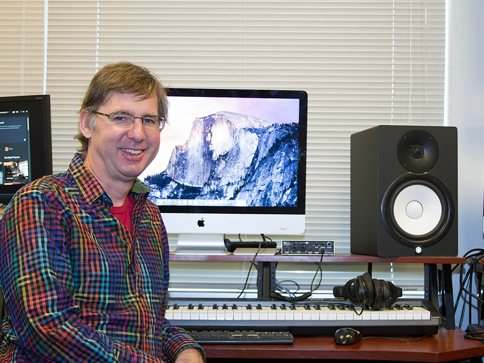 DigiPen music senior lecturer Brian Schmidt sits in front of a computer in the DigiPen sound lab