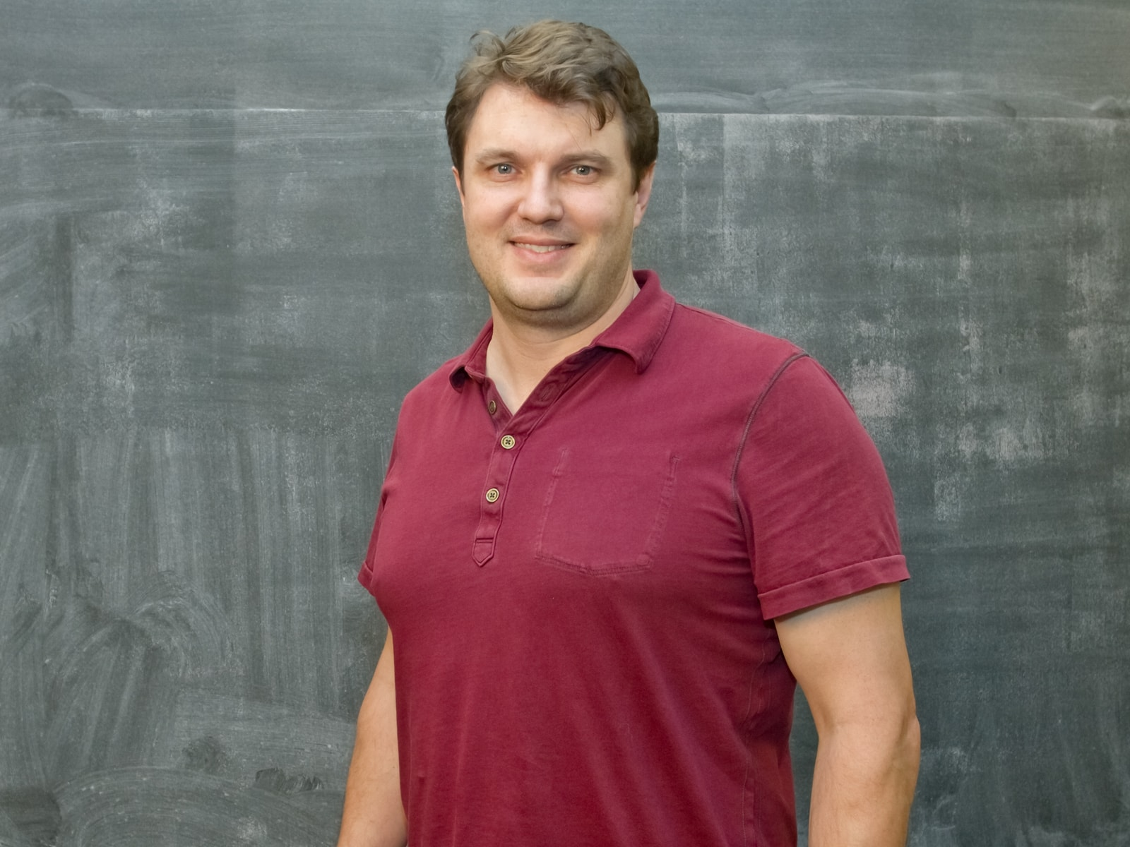 DigiPen physics professor Charles Duba smiling in front of a blackboard