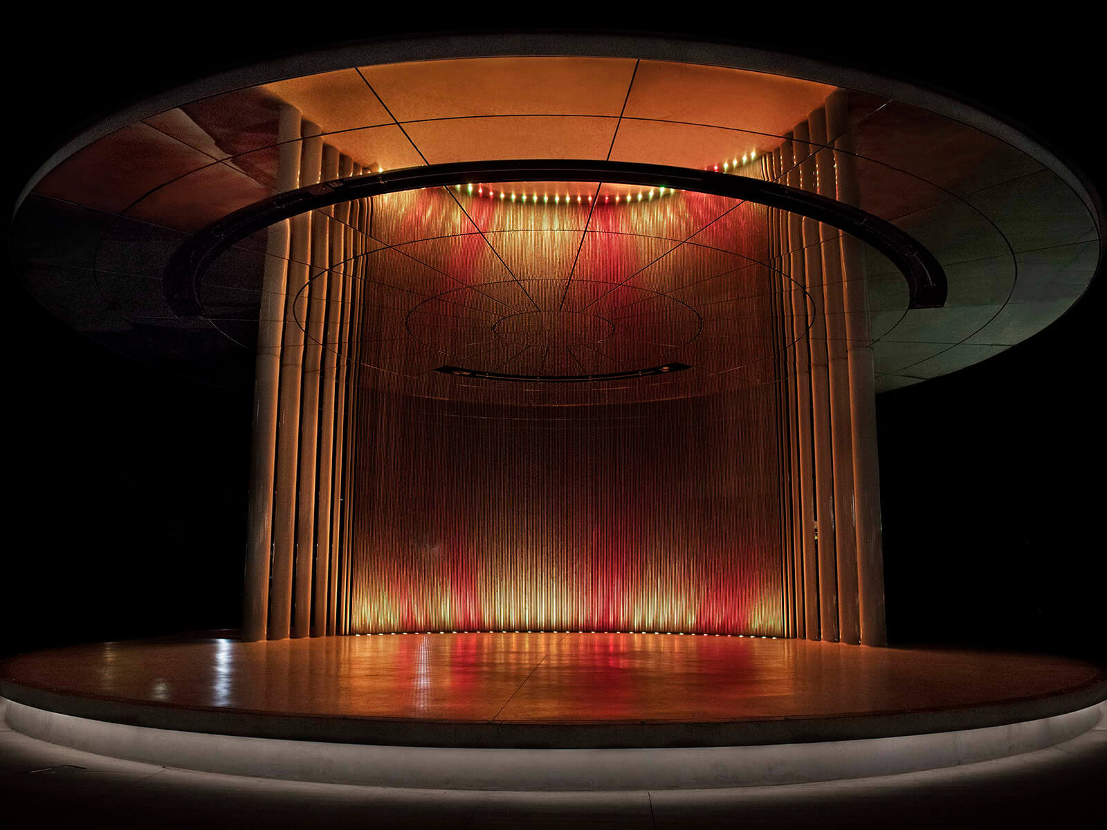 A circular structure with 380 etched metal rods lit in shades of red and yellow at night