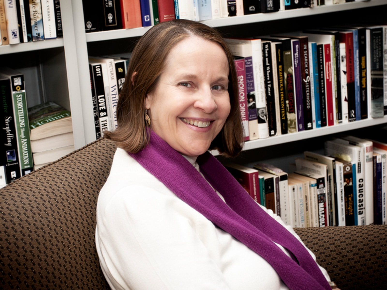 Portrait of DigiPen humanities professor Claire Joly in front of bookshelves in the campus library