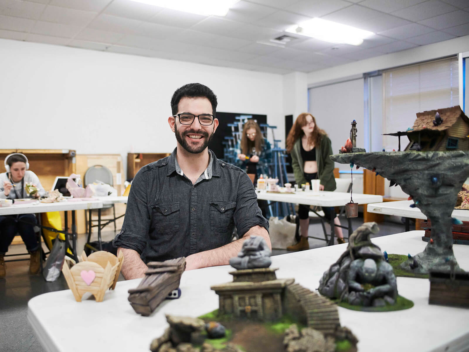 Professor Danny Samuels poses in front of student work in his miniature set design class.