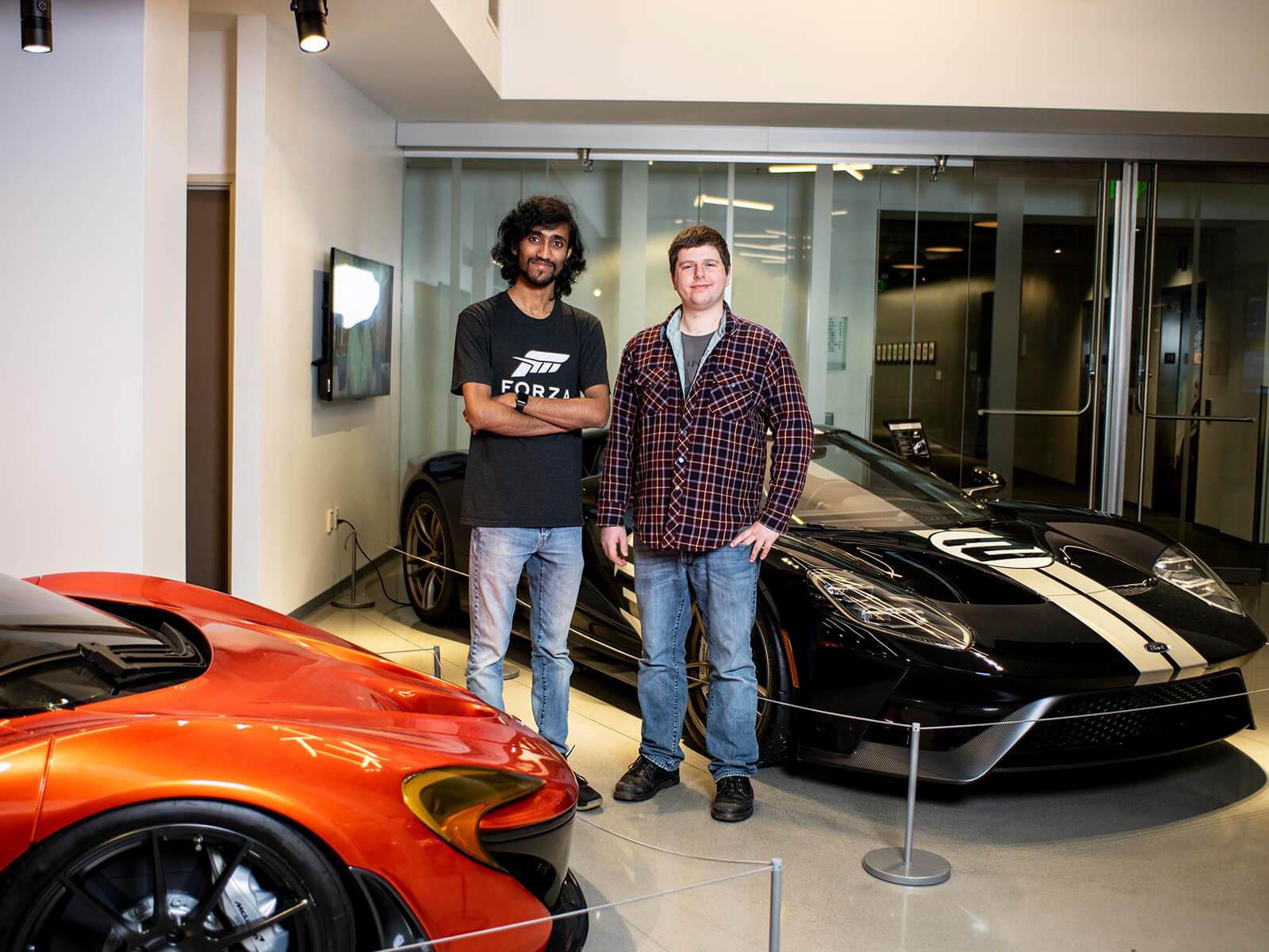 Michael Pitaniello and Deepak Chennakkadan stand next to luxury cars in the Turn 10 Studios lobby.