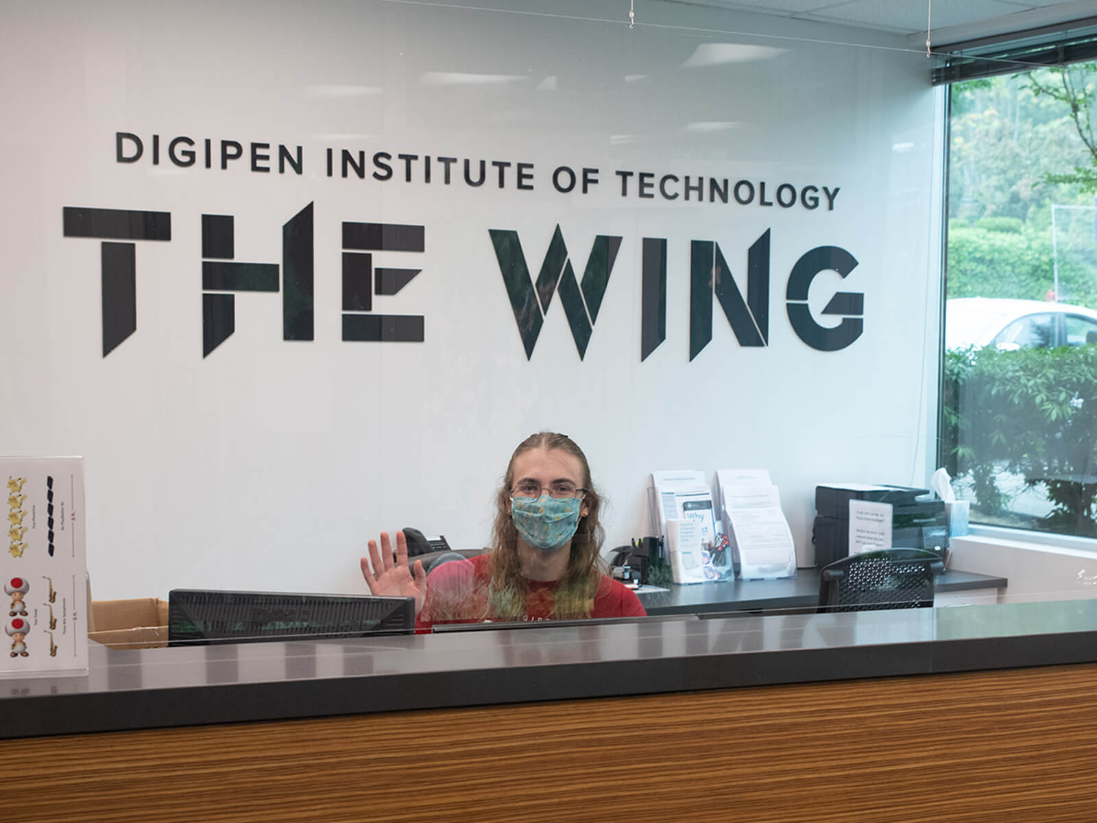 Two masked students wave at the front desk of DigiPen's new campus expansion, The Wing.