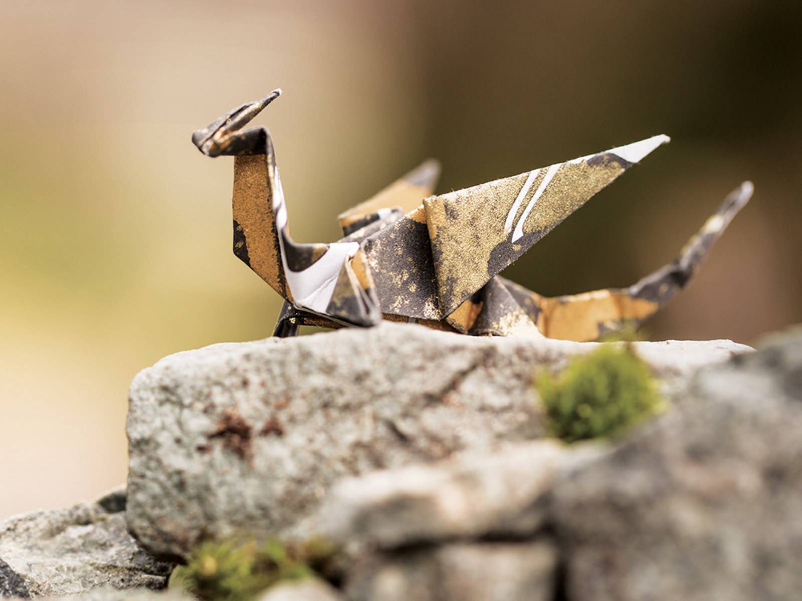 A gold and black origami dragon sitting on a mossy rock against a green background