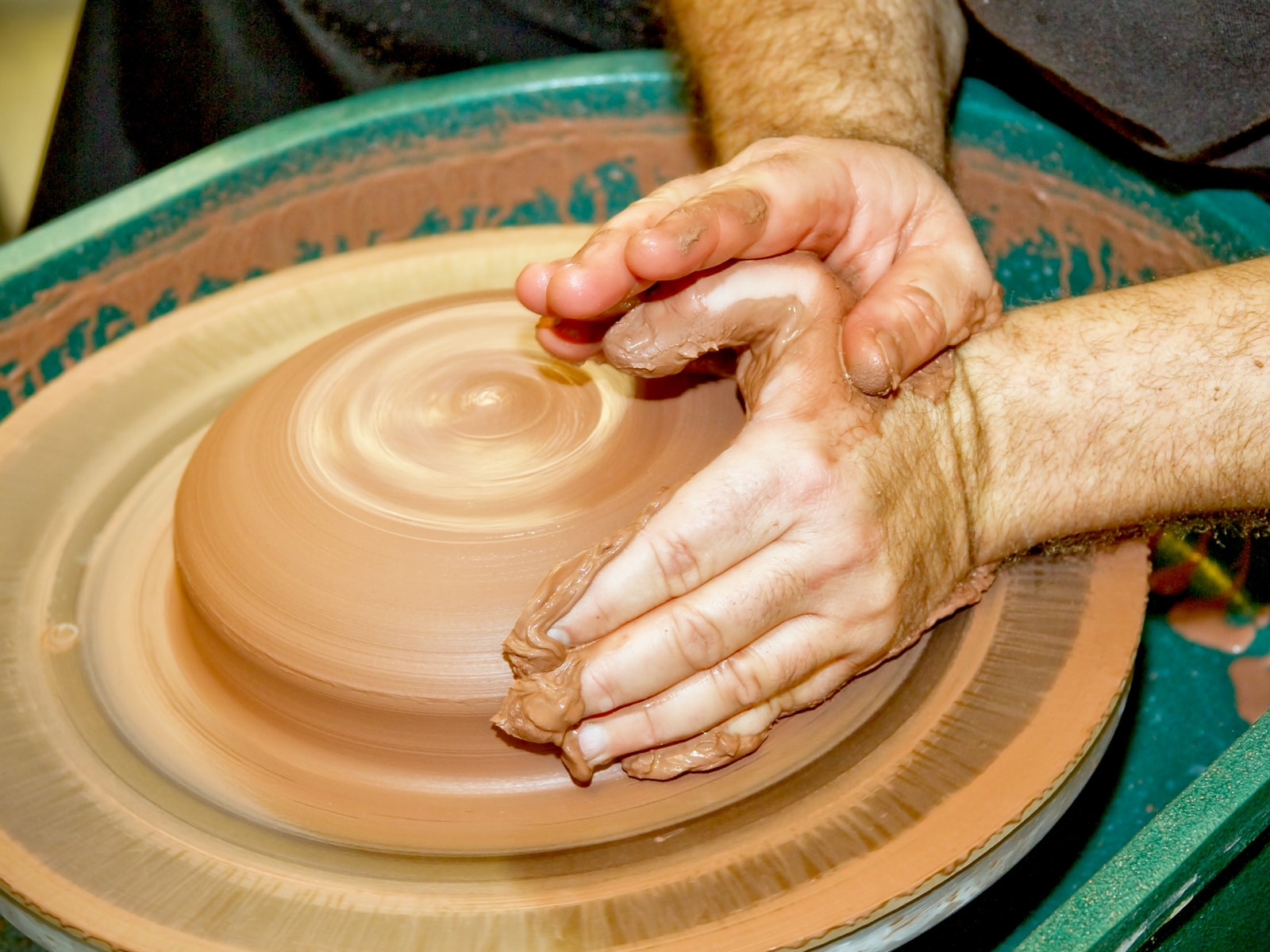 Hands molding clay on a spinning wheel in the new DigiPen ceramics studio
