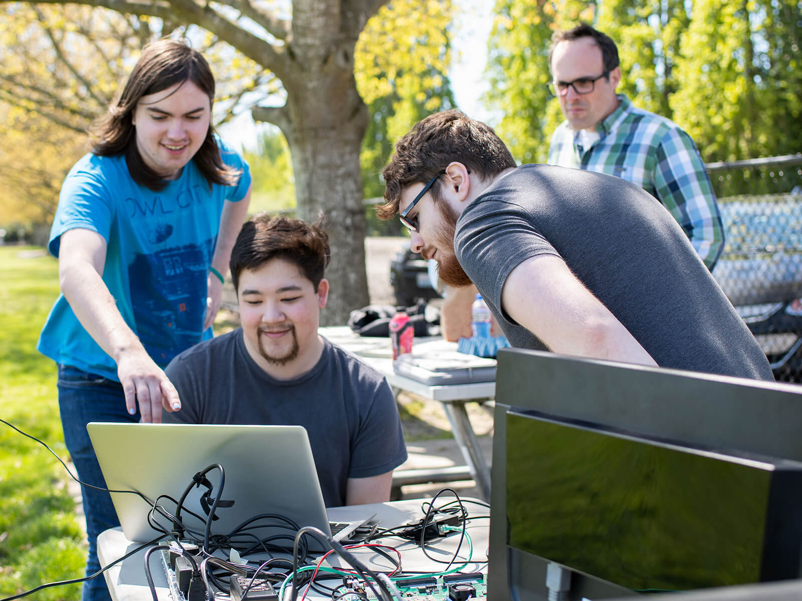 Two students look over the shoulder of another at a laptop computer and radar system set up outdoors in a park.