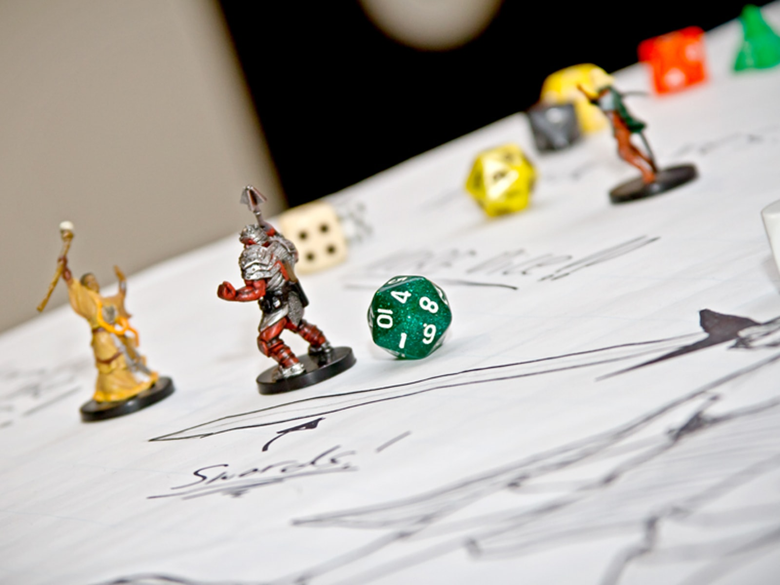 Close-up of board game figurines and 10-sided die