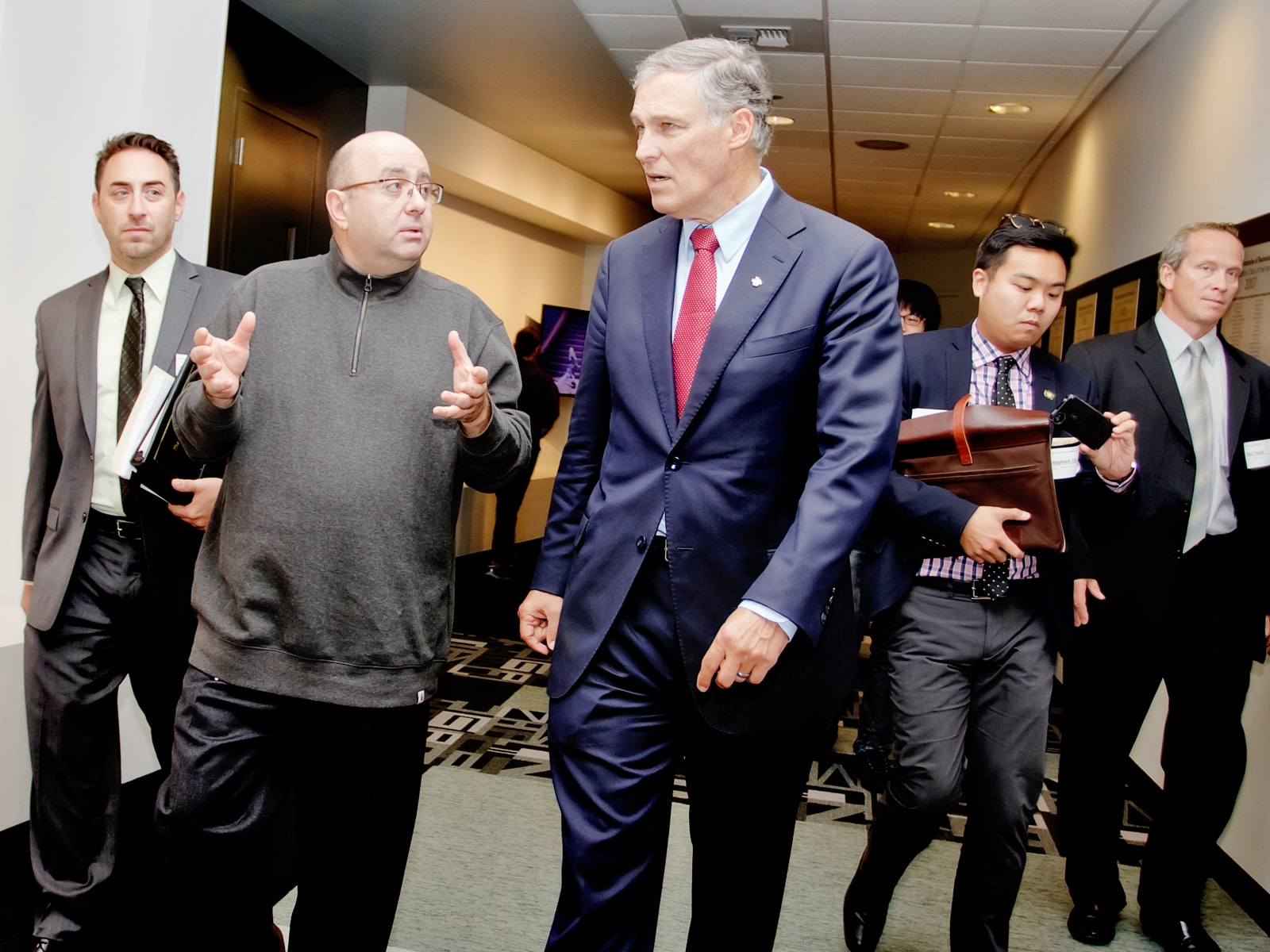 DigiPen founder Claude Comair and Washington Governor Jay Inslee walking down the hall surrounded by staffers