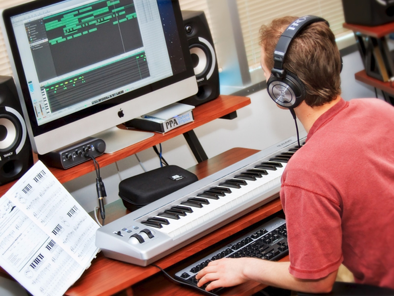 DigiPen sound design student composing music with a computer and a digital piano keyboard