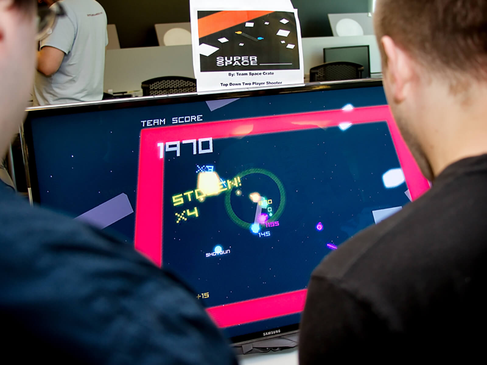 Over-the-shoulder view of two people playing the game Super Space ____; blocks and numbers float in space on a TV screen