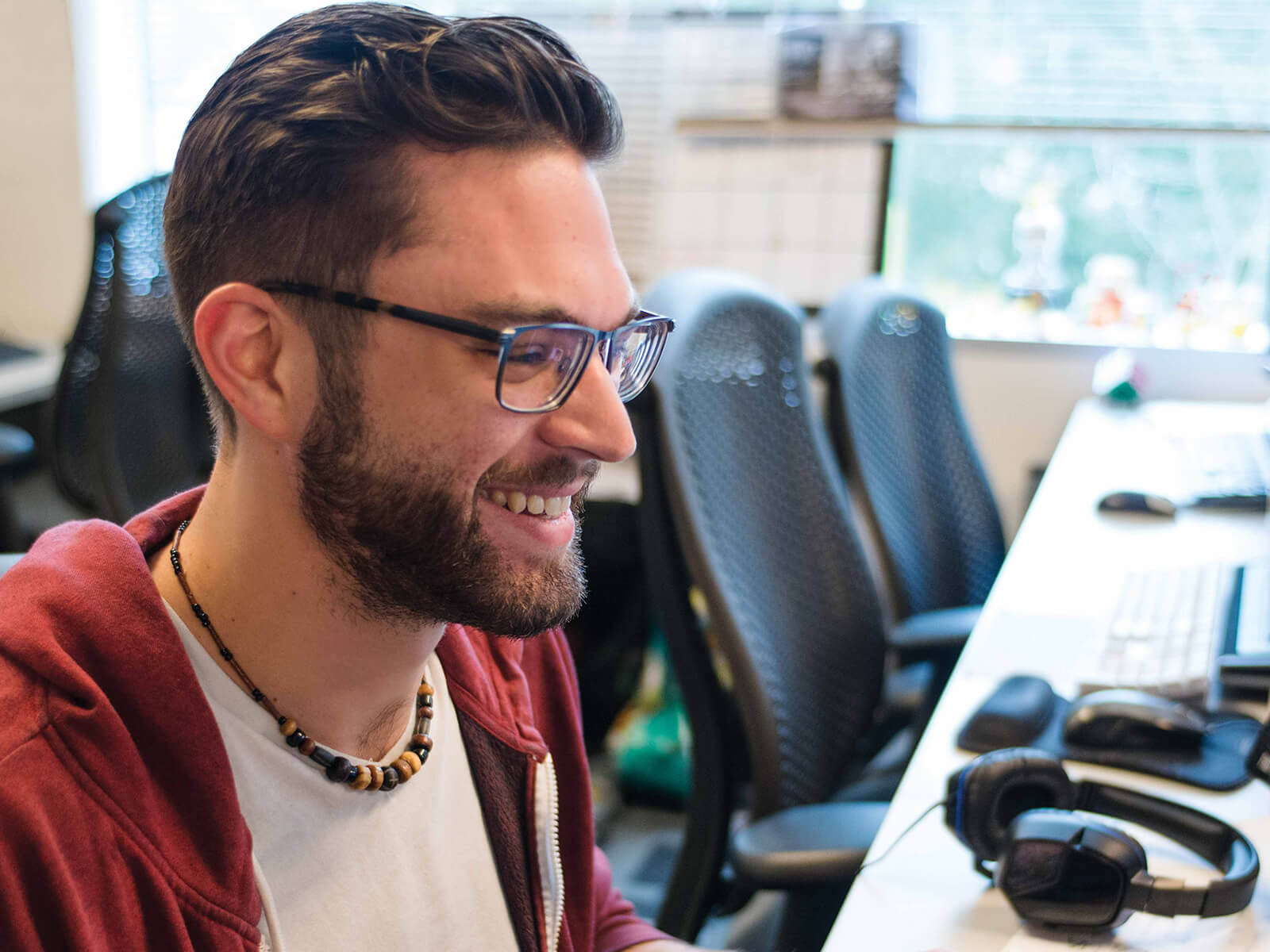 A student wearing glasses sits in a computer lab smiling at his computer screen.