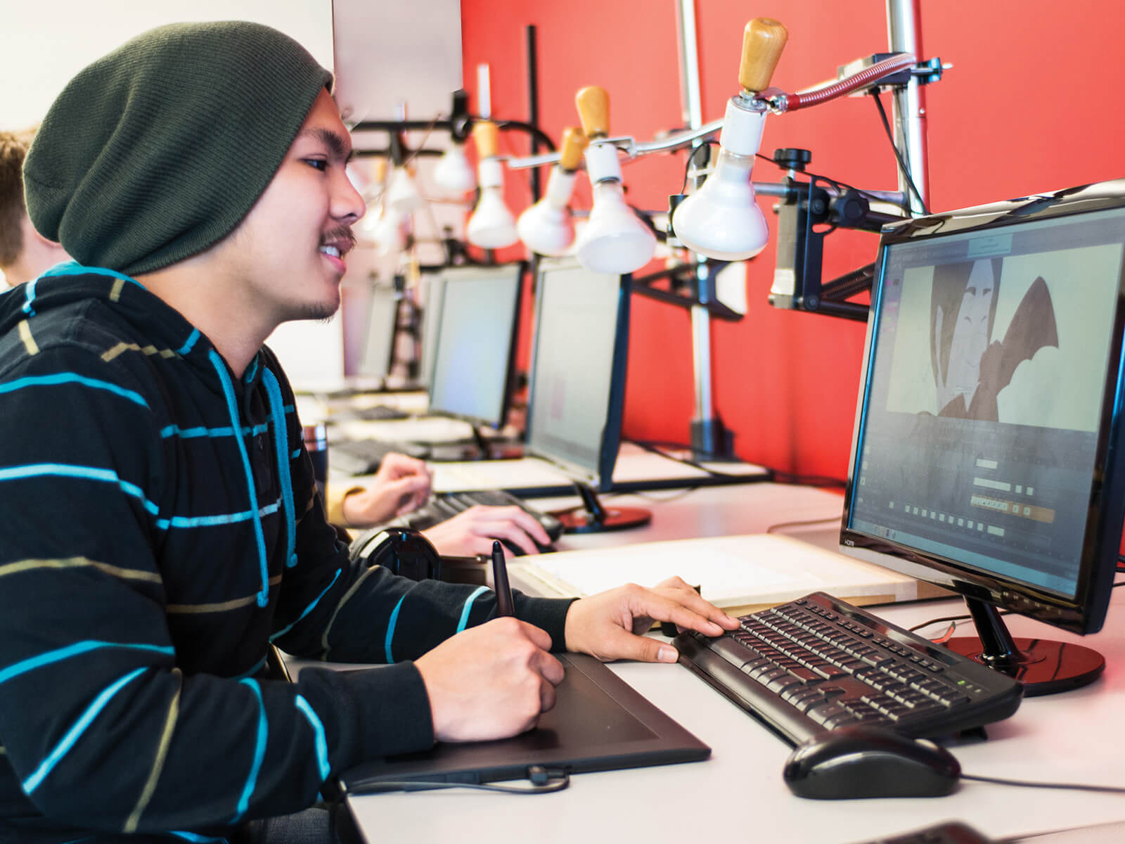 A DigiPen student works with a drawing tablet in front of a computer screen