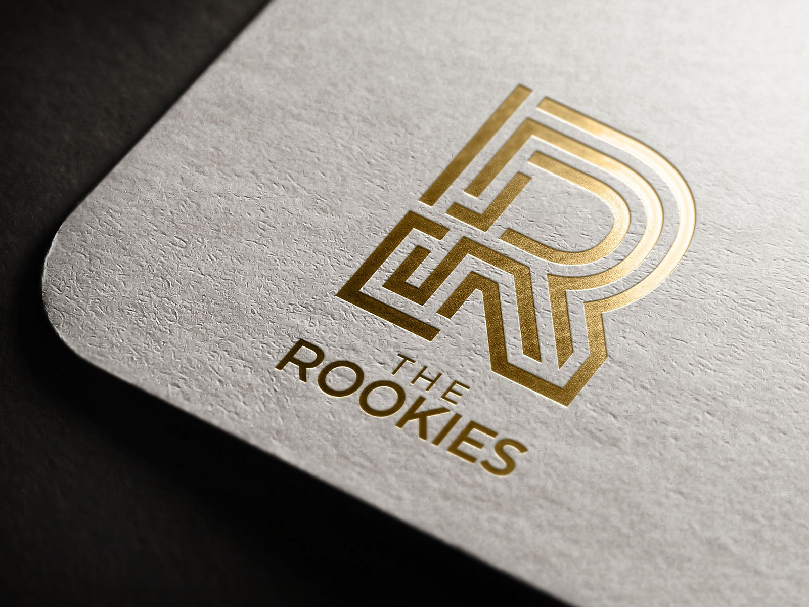 """Golden """"R"""" logo for the Rookies imposed near corner of grey paper"""