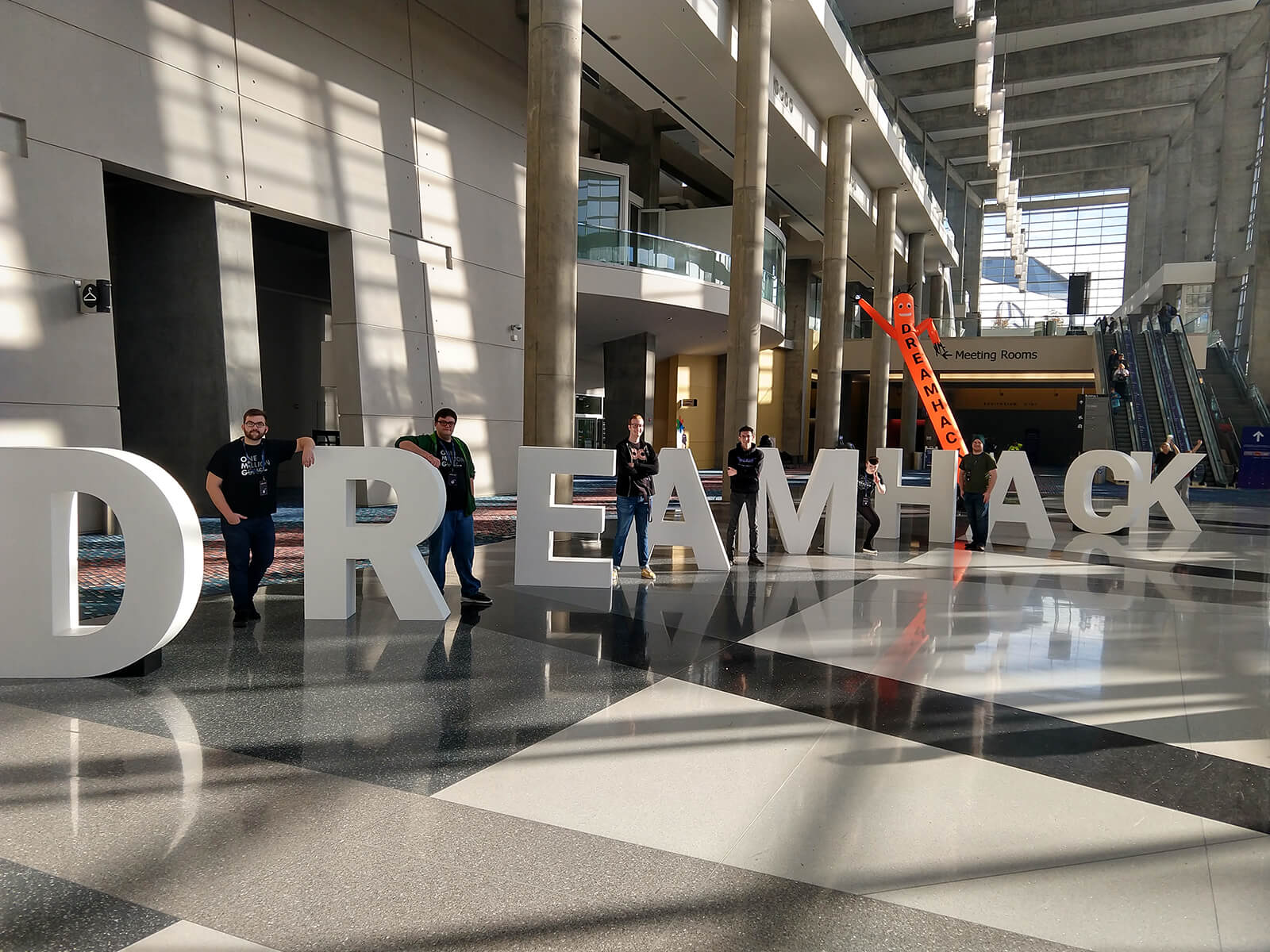 Six DigiPen students stand next to giant letters that spell out 'DREAMHACK'
