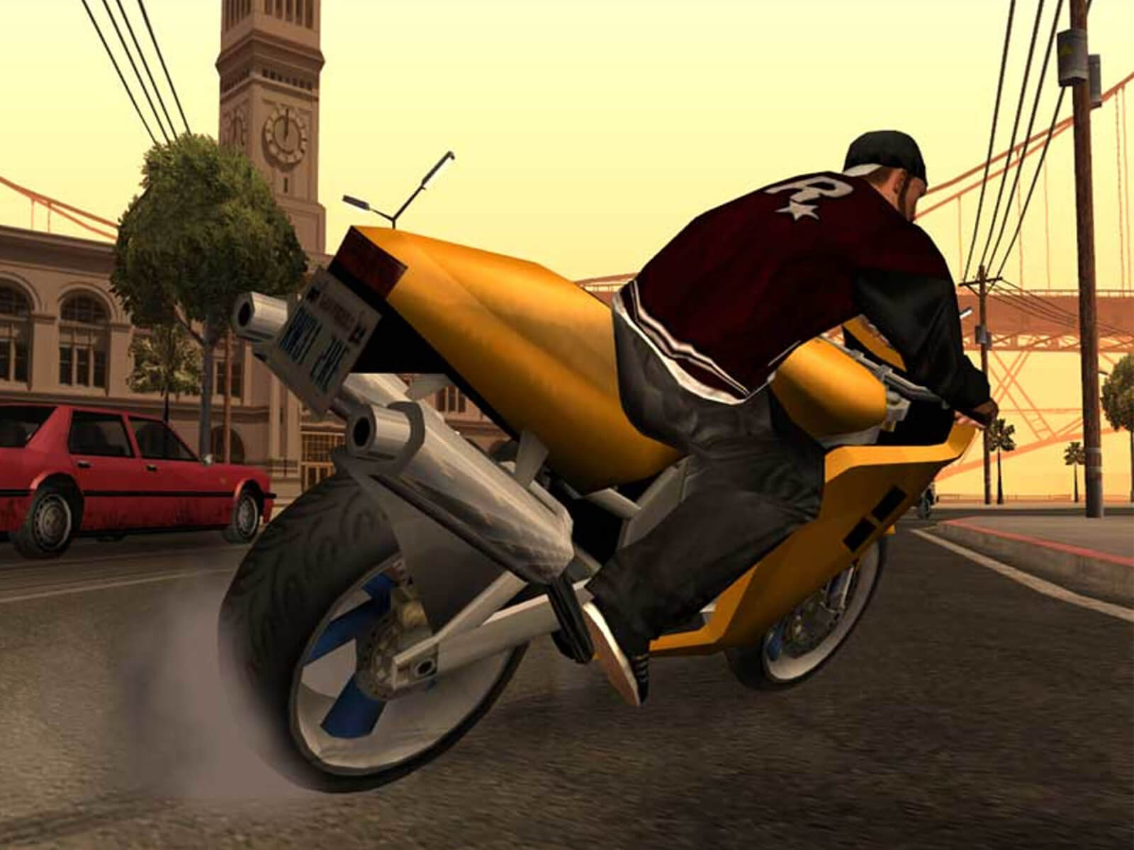 A screenshot from Grand Theft Auto: San Andreas of a man in a jacket with the Rockstar logo on it riding a gold motorcycle.