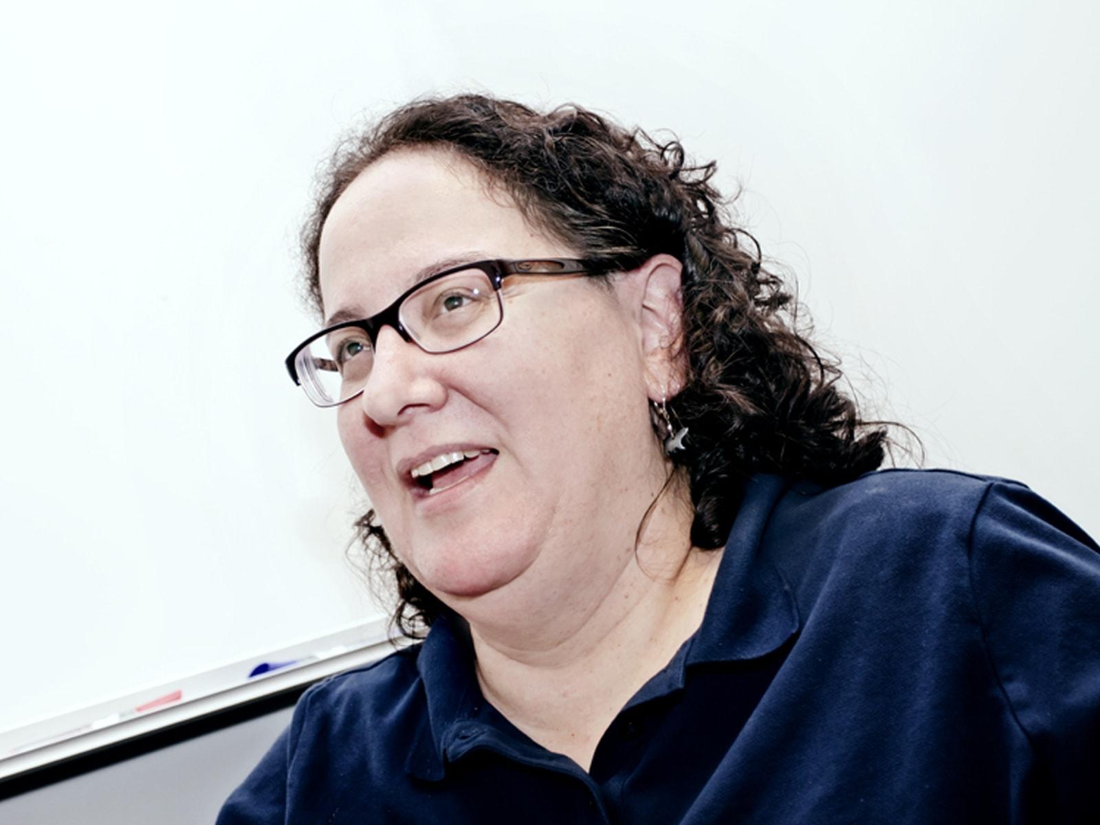 DigiPen professor Ellen Beeman speaking in front of a whiteboard