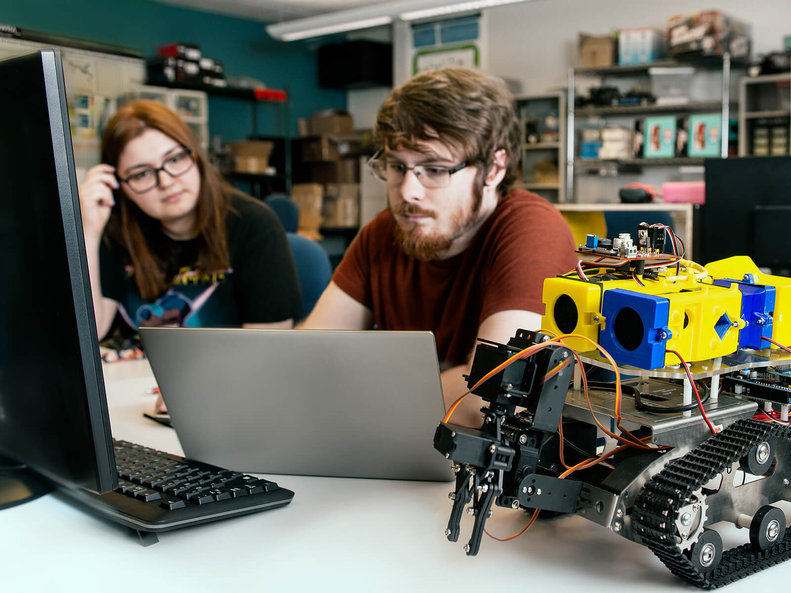 DigiPen engineering students sit next to an self-navigating robot.