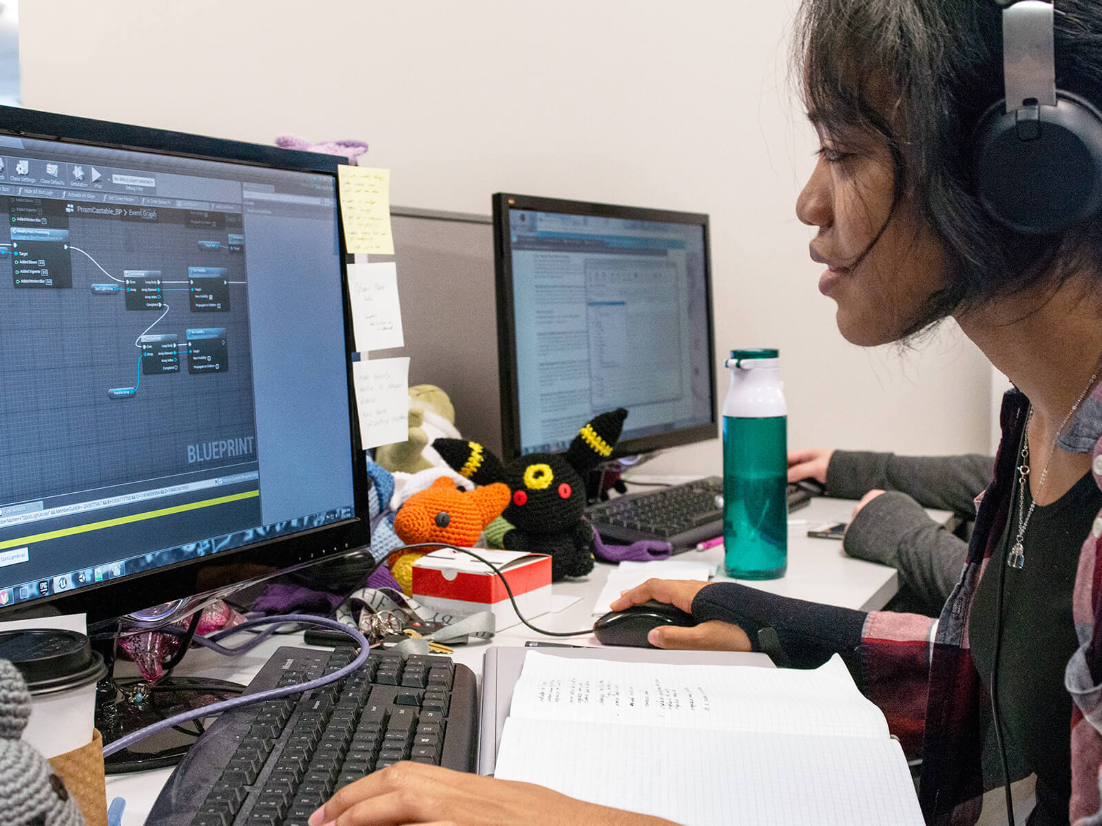A DigiPen game design student works on her computer surrounded by knit plush toys.