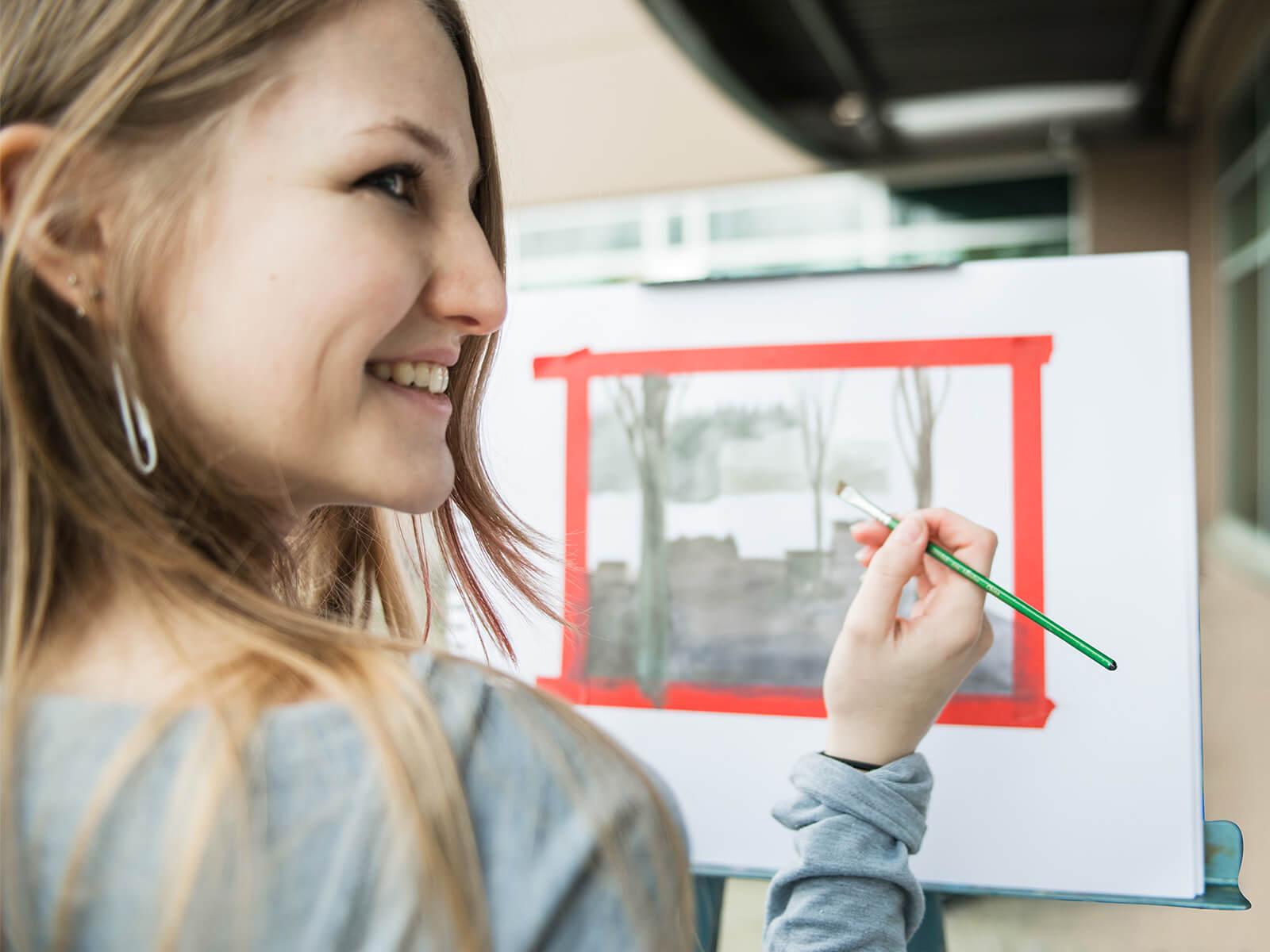 A DigiPen art student paints a watercolor landscape.