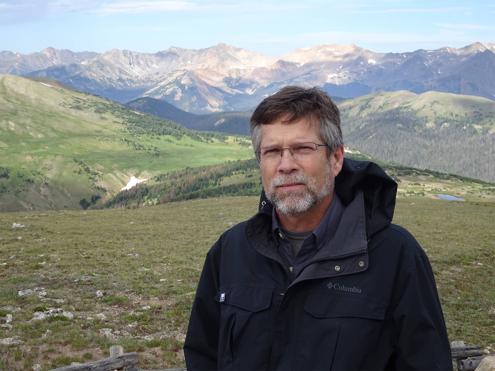Professor James Peet stands in front of a vast valley and mountain range.