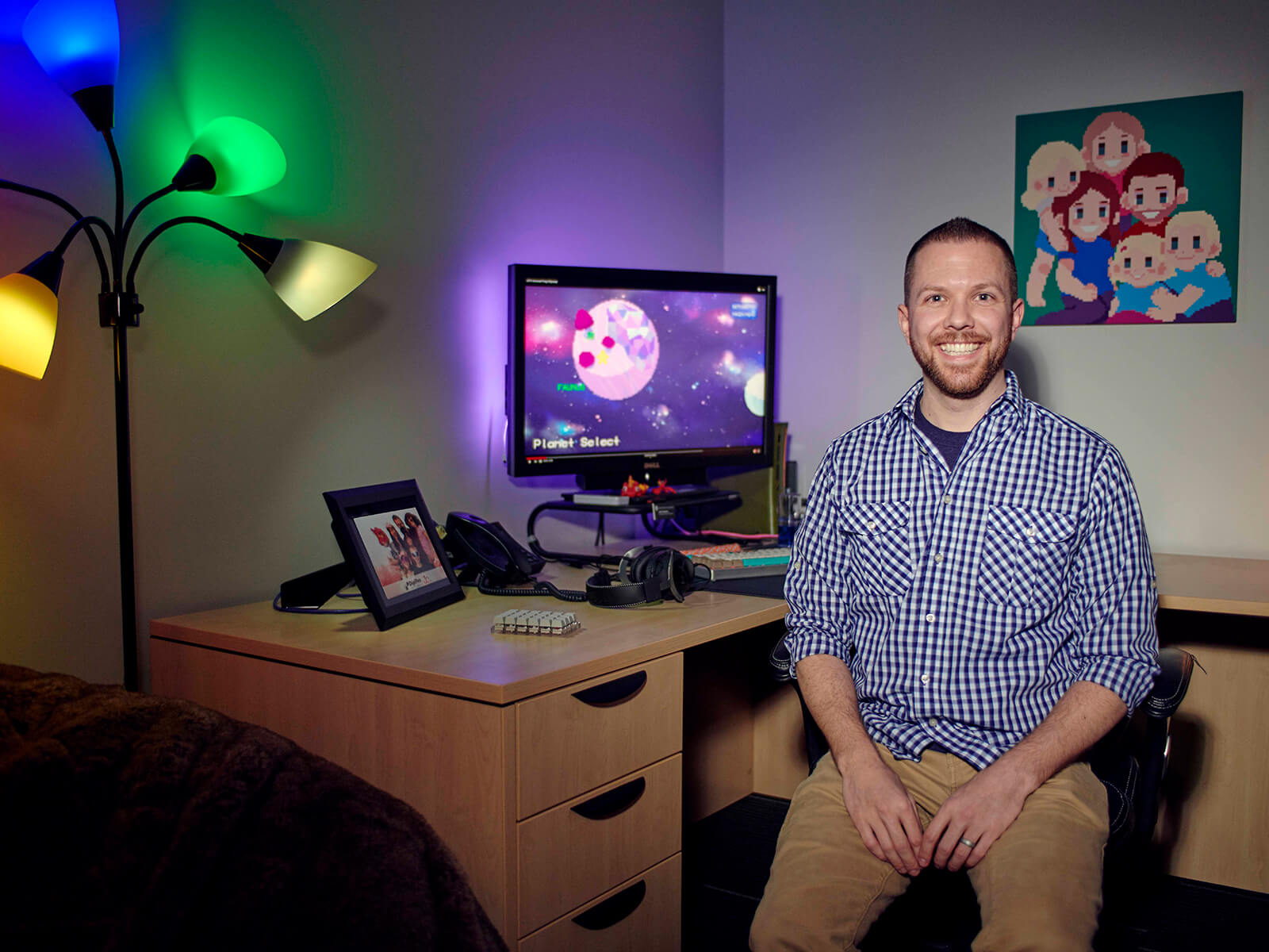 Justin Chambers smiles facing camera at his office desk, dark room decorated with objects and illuminated by colorful lamps.