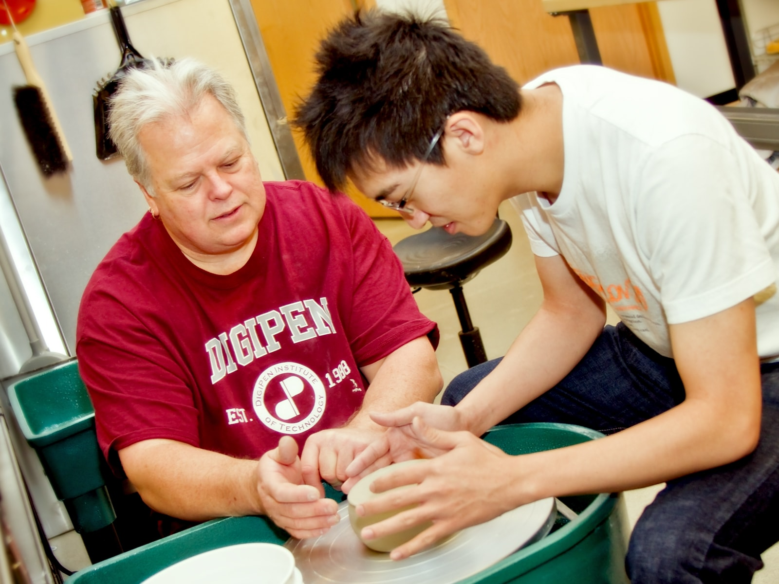 DigiPen fine arts lecturer Ken Turner works with a student on a ceramics wheel