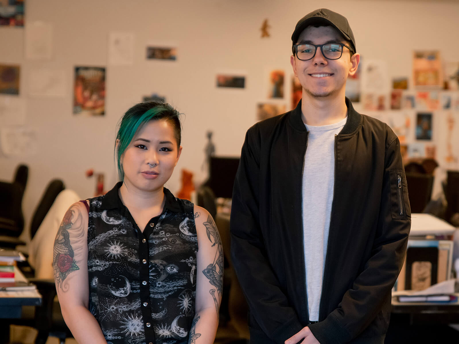 "Trang ""Sushie"" Ta and Jesse Munguia stand next to each other in the DigiPen MFA lab."