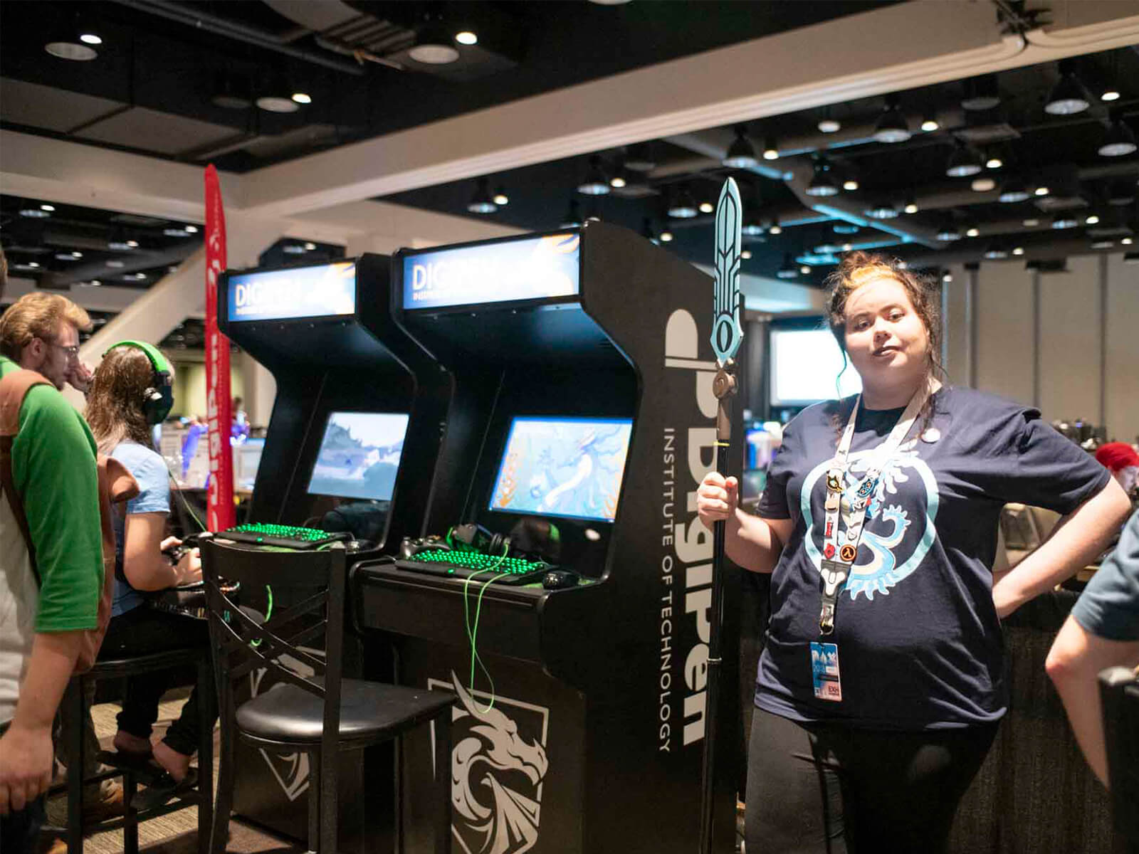 A DigiPen student staffs the PAX DigiPen arcade, cosplay spear in hand.